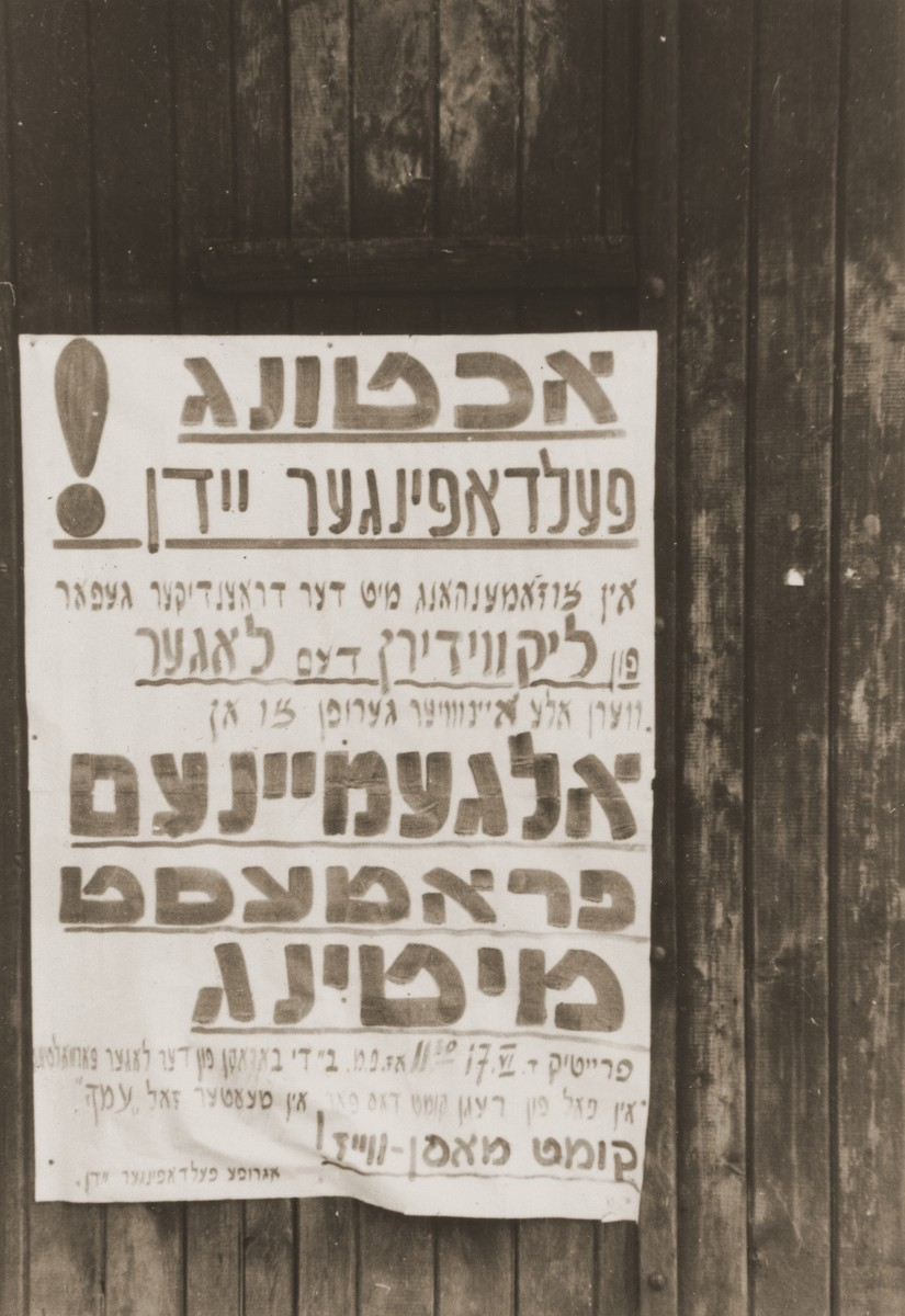 Announcement posted on the outside of a building in the Feldafing displaced persons camp calling upon residents to attend an open meeting to protest the impending liquidation of the camp.