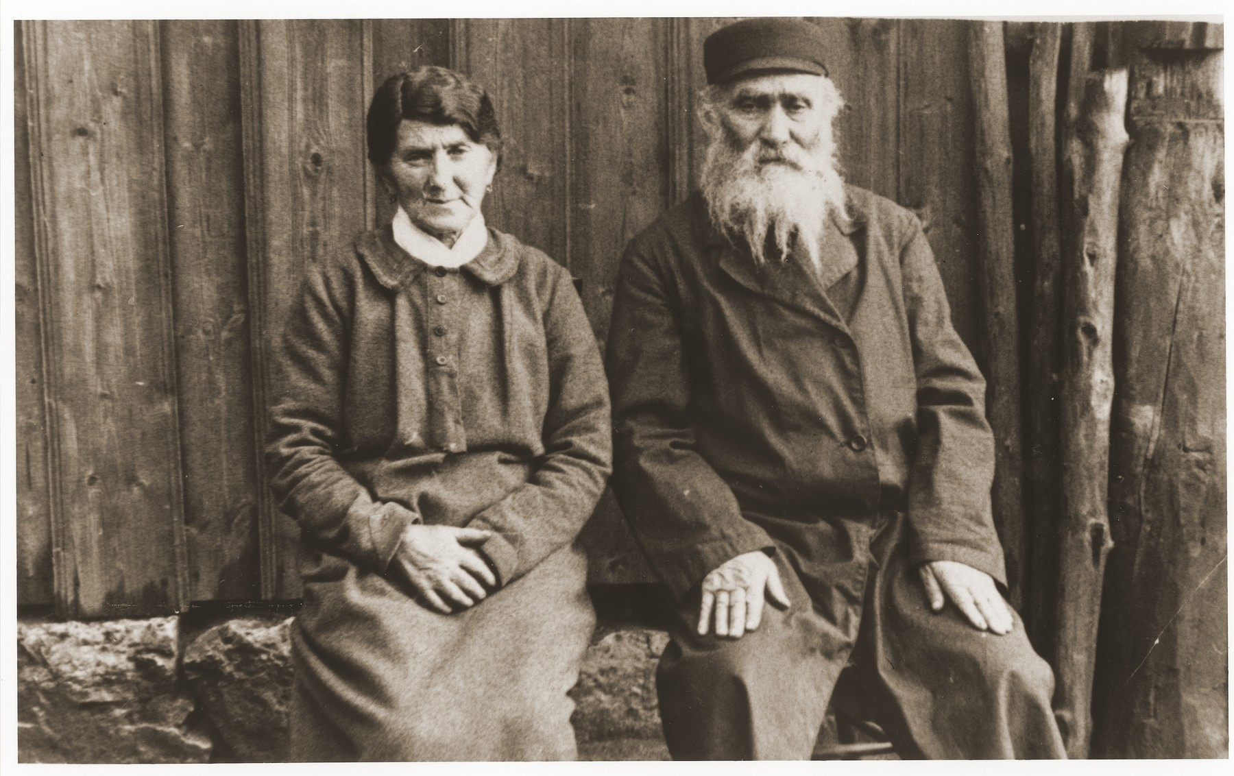 Portrait of an elderly Jewish couple seated outside in the Strzemieszyce Wielkie ghetto.  Pictured are Laja and Symcha Korzuch, the grandparents of David Bajtner.