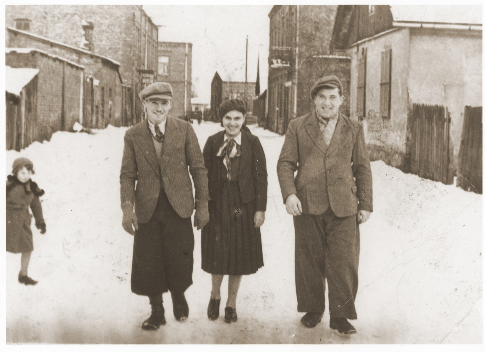 Mendel-Ajzik, Cesia and Abram-Zelig Kleiner walk down a snow covered street in Lazy, Poland.