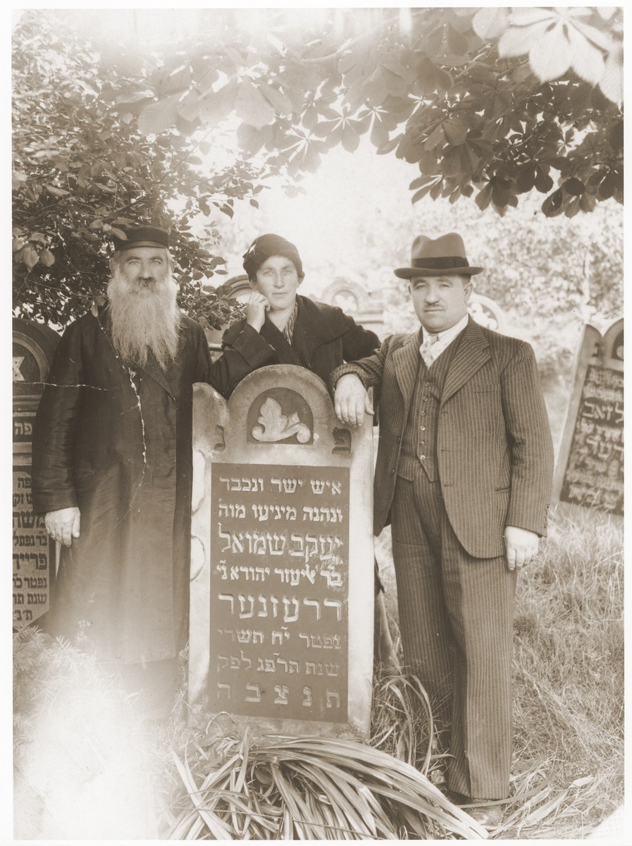 Chaim-Szaje Dresner, accompanied by his children Mala Dresner Kleiner and Szlomo Dresner, stands next to the tombstone of his father, Yaakov Shmuel.