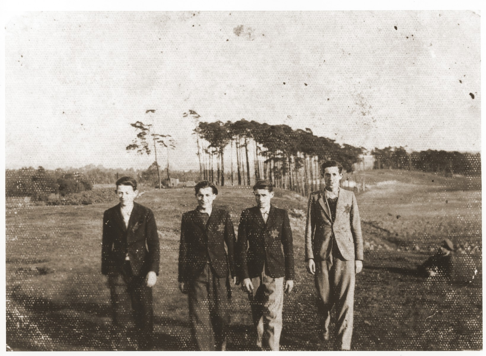 Four young Jewish men wearing yellow stars walk in an open field in the Strzemieszyce ghetto.  Pictured from left to right are: Szmil Kohn, David Bajtner, Dawid Moszkowsi and Aron Kohan.