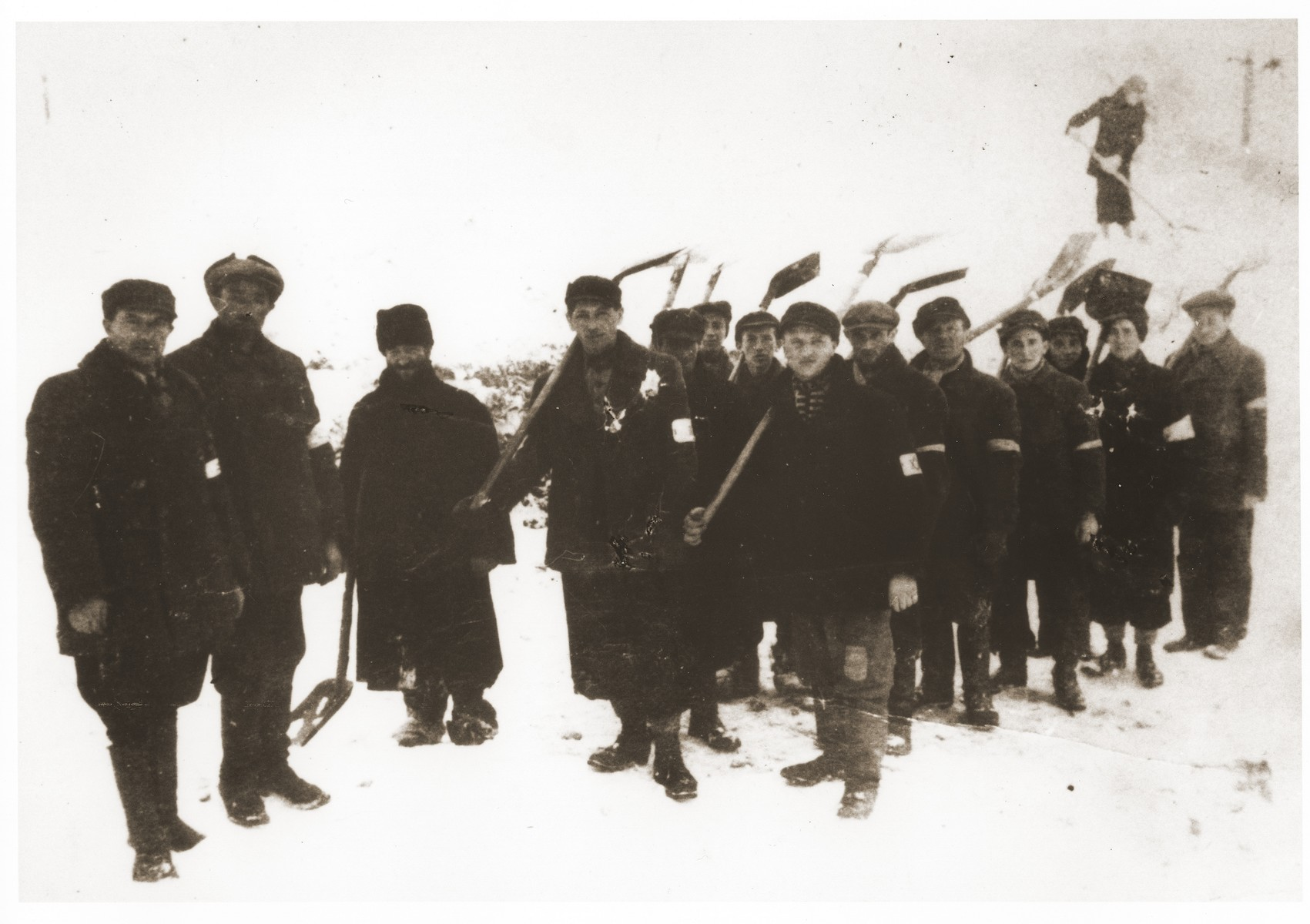 Jewish laborers wearing armbands are forced to shovel snow in Slawkow, Poland.  Chaim Szlojme Imerglik is on the far left. Also pictured is  Joseph Gleitman, the fourth person from the left.