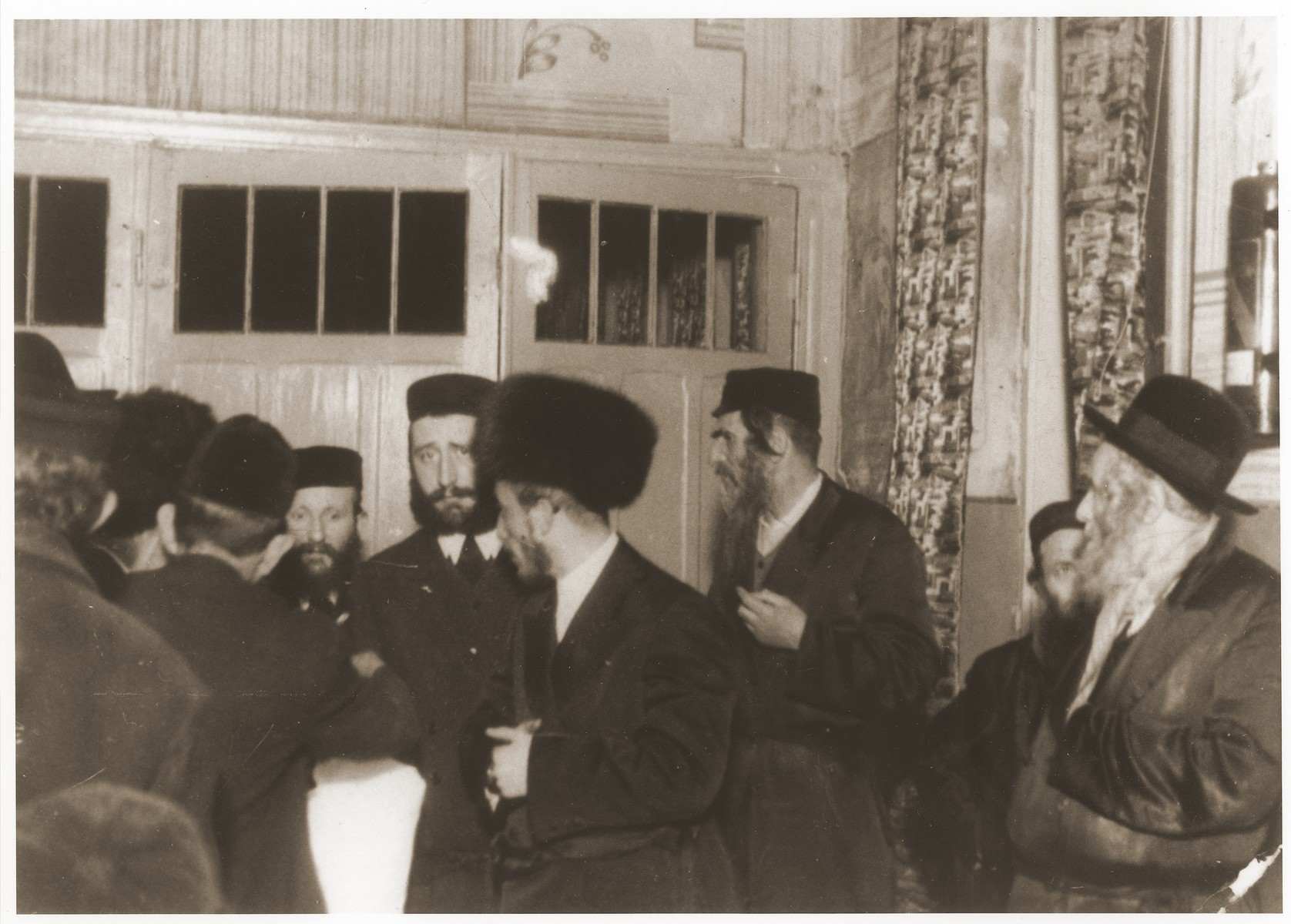Ger Hasidim, including the rebbe, gather to greet  bridegroom before a wedding.  Among those pictured are Abram Mordche Kopelman and Symcha Binem Alter.
