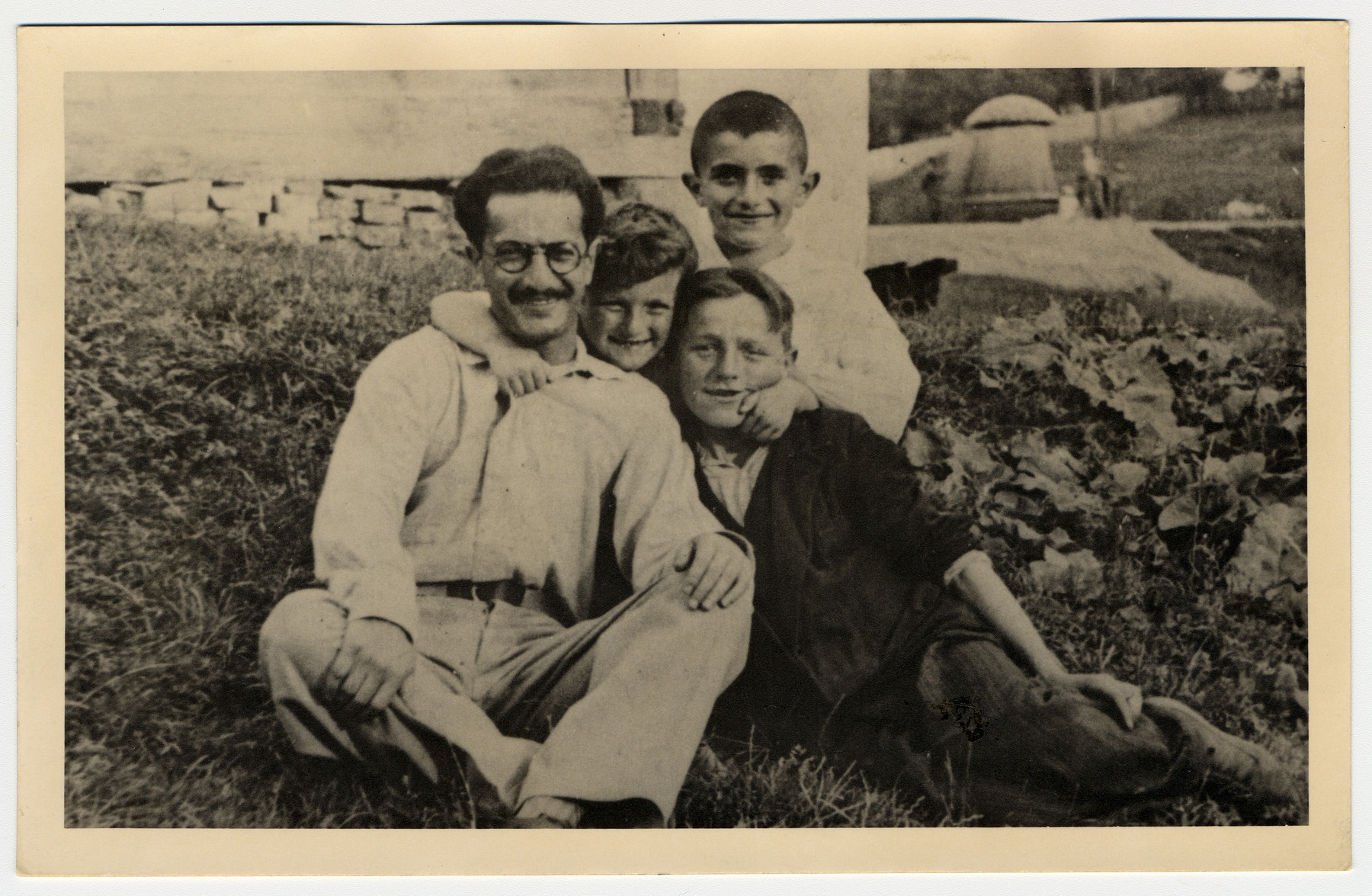 Close-up portrait of a man and three boys sitting in a field in Drohobycz.    Paul Lustig is pictured in the back.  [With him may be his uncle and cousins.]