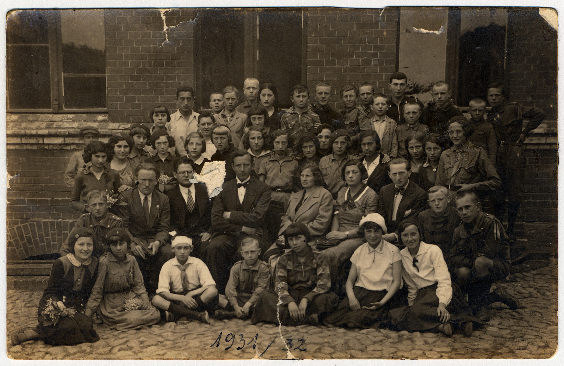 Group portrait of children and teachers in a Jewish school in Poland [possibly the Jewish Gymnasium in Mlawa].  Issachar Fater is seated in the second row, third from the left.