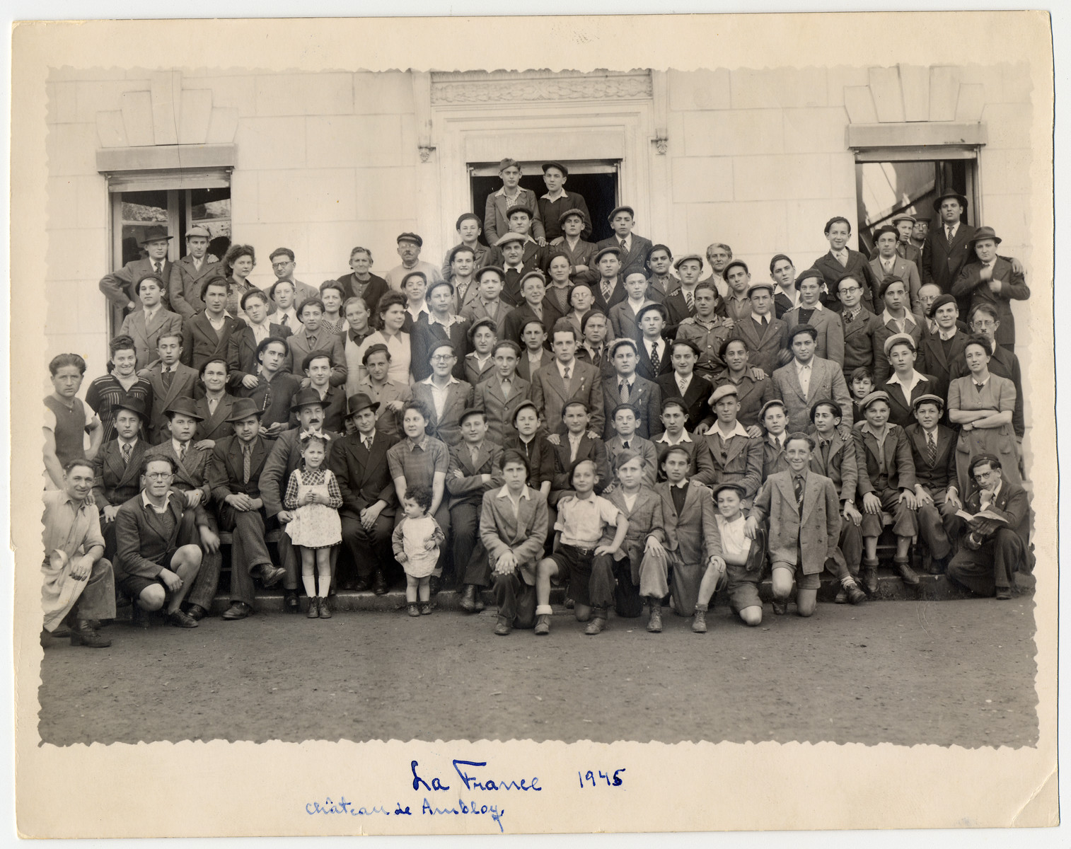 """Group portrait of the staff and boys of Ambloy, an OSE home for religious youth.  Among those pictured are (First row, left to right): Natan Szwarc, Izio Rosenman, Deblin, unknown and Berek Rybsztajn.  (Third row): Abraham Tuszynsky (2nd from left, first boy next to woman), Andre Zelig is in the center with a tie and his hands on the boy in front of him and Elie Wiesel (second right of Tuszynsky).  Binem Wrzonski is to the right of Elie Wiesel.  The donor, Jakob Rybsztajn is in the fourth row, fifth from the left.  Pictured in the center to the right of the woman in white is Motjes Kaufman.  The inscription on the back reads """"Before our departure from Chateau Ambloy for Paris""""."""