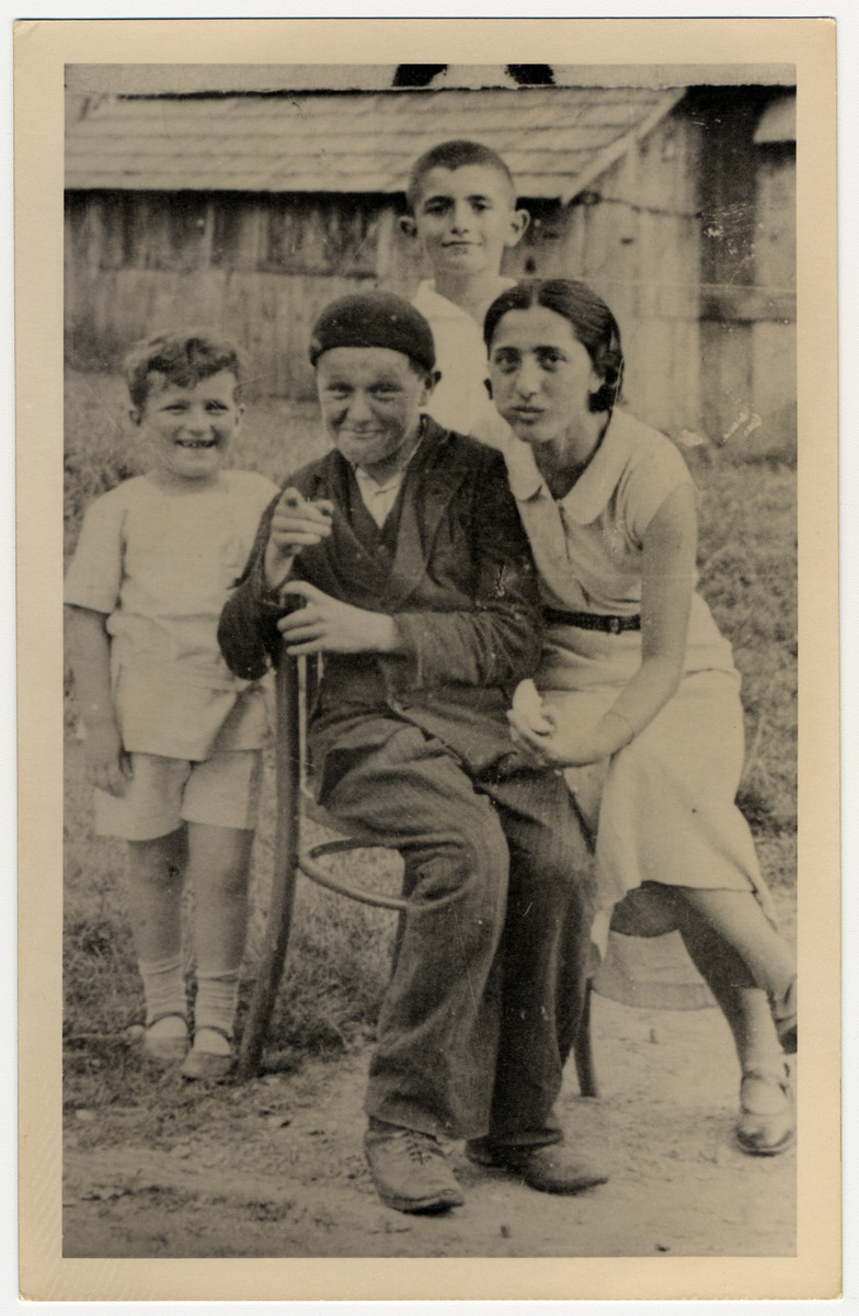 Portrait of four Jewish children and teenagers posing outside a wooden house in Drohobycz.  Pictured in the back is Paul Lustig.