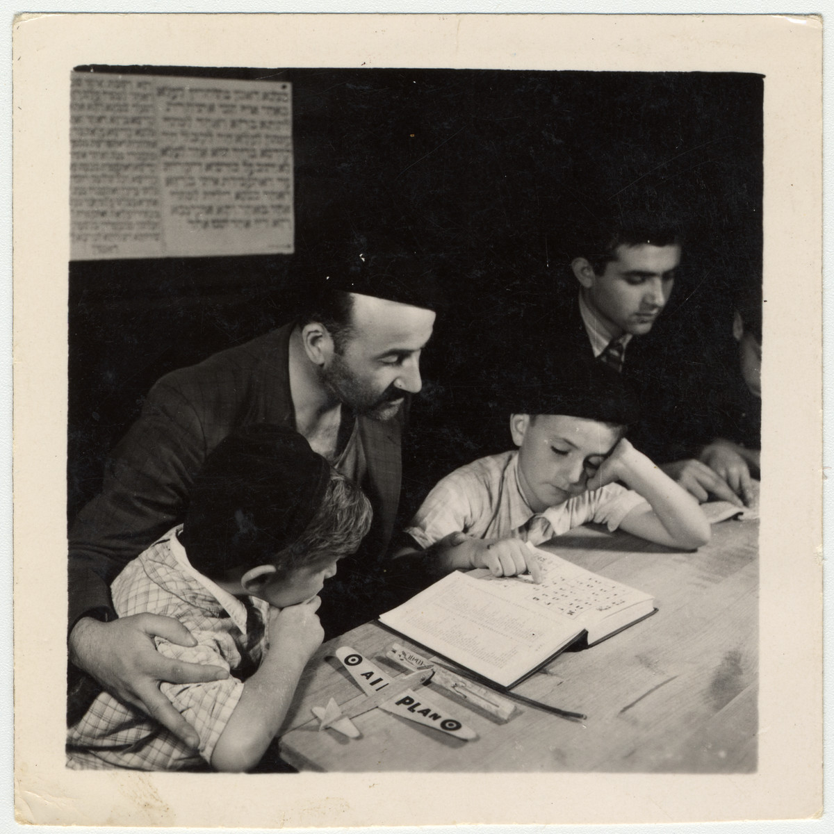 Buchenwald child survivor study a Hebrew text at an OSE (Oeuvre de Secours aux Enfants) children's home in France [either in Ambloy or Taverny].  Among those pictured is David Perelmutter who was born on January 8, 1937 in Lodz.
