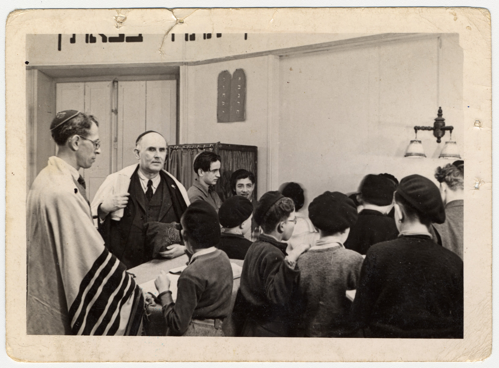 Jewish boys gather for a prayer service in a chapel in an OSE children's home.  Those pictured include Elie Wiesel (seen in profile, back right) and Jakob Rybsztajn standing next to him facing the camera.