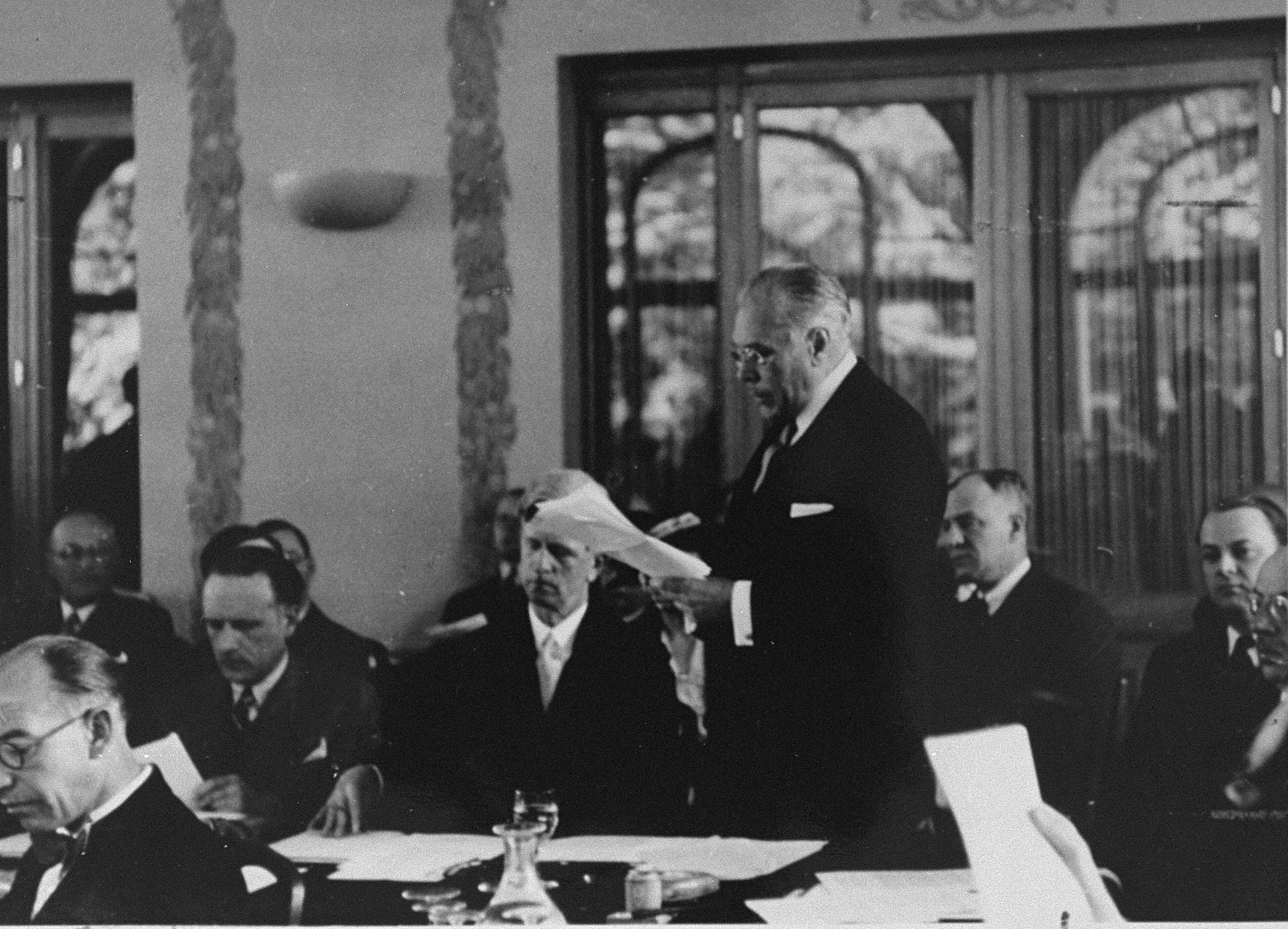 Myron Taylor addresses the International Conference on Refugees at Evian-les-Bains.  James Grover McDonald is seated next to him.  On the far right edge of the picture is Robert Thompson Pell, an assistant to Myron Taylor at State.  The man looking down, second from left of Taylor, with a dark tie and mustache is Georges Coulon.