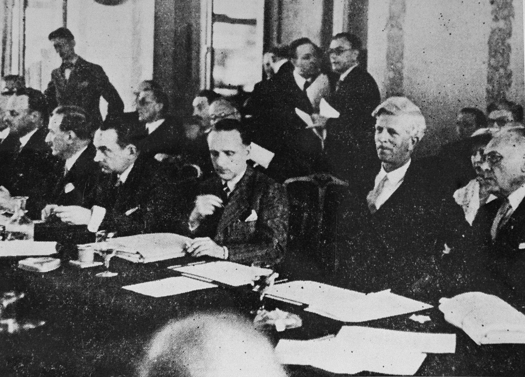 Delegates attend a session of the International Conference on Refugees at Evian-les-Bains.  Among those pictured are: Myron C. Taylor (right); James McDonald (second from the right); Norman Bentwich (left) in conversation with Henri Berenger.