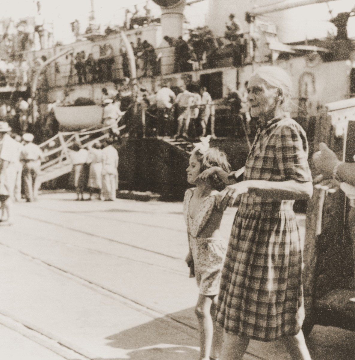 An elderly woman and her granddaughter, who have just arrived in Haifa on board the Mala immigrant ship, walk along the pier.