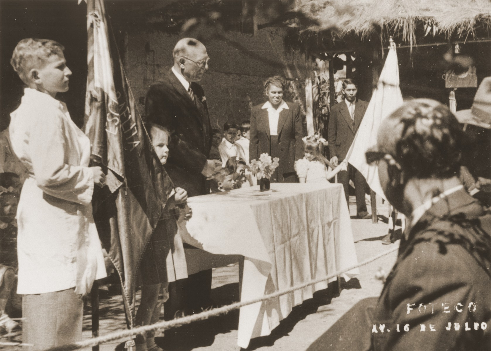 The principal of the Escuela Boliviana Israelita (the Jewish primary school in Bolivia) delivers a speech at an outdoor graduation ceremony.  Among those pictured is Elly Spitzer (second from the left, holding the flag).