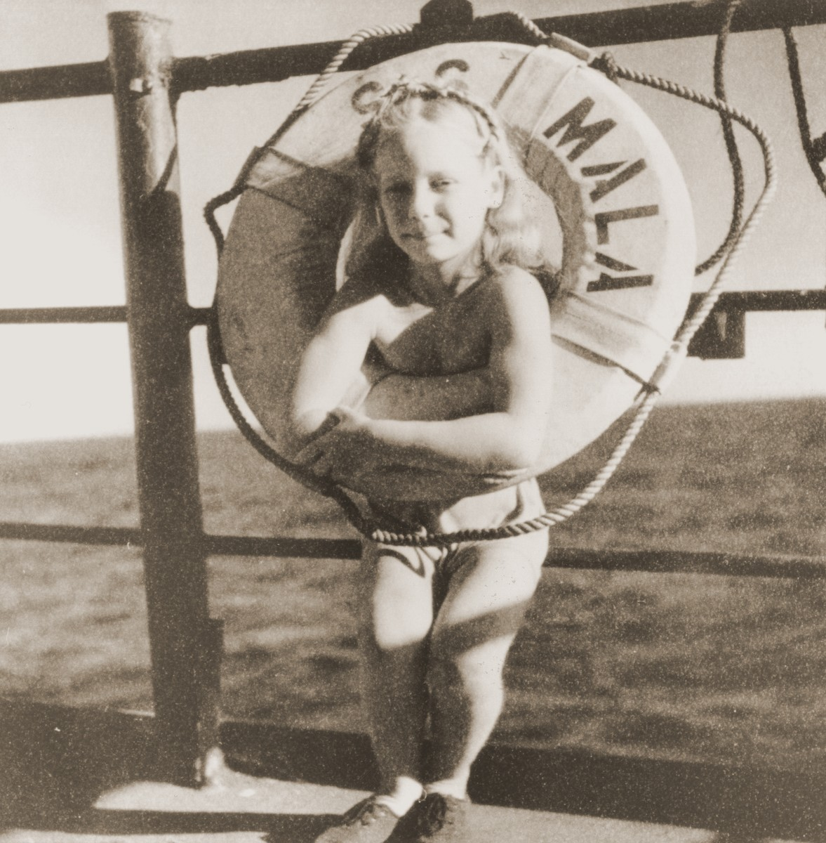 A girl poses in the life preserver on the deck of the Mala immigrant ship.