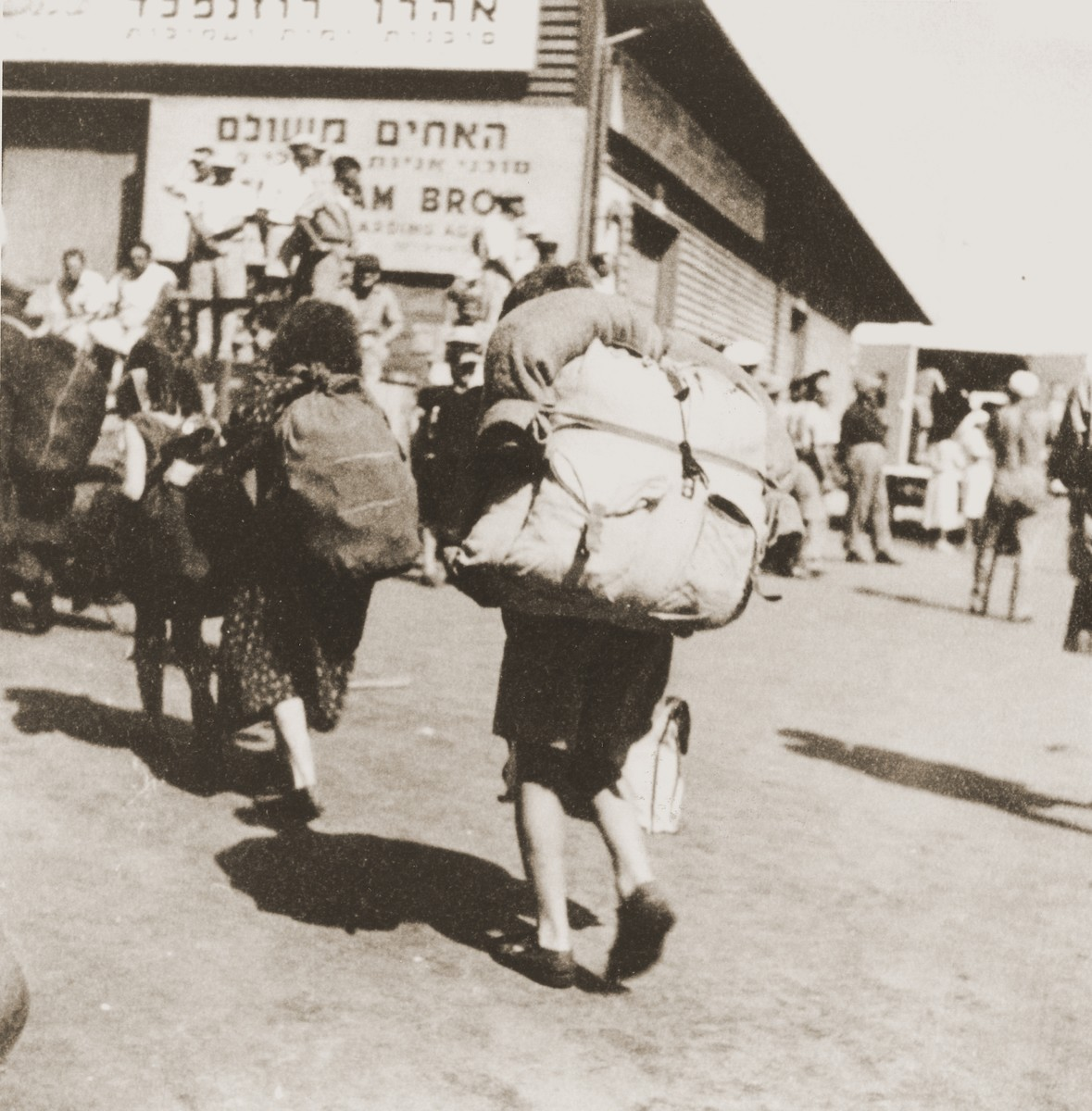 Jewish DPs who have just arrived in Haifa on board the Mala immigrant ship, walk along the pier with their total belongings.