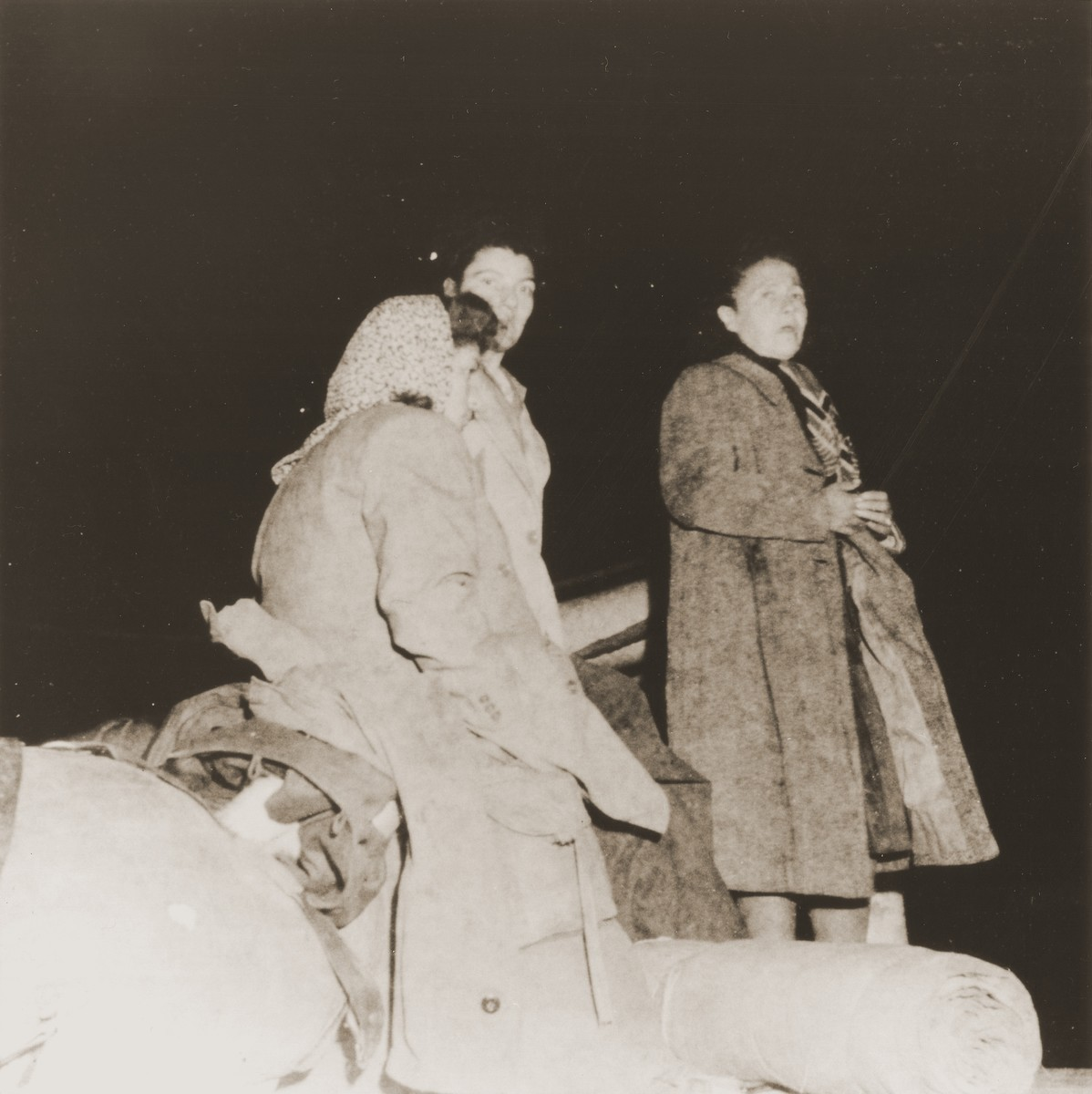 Female passengers, wearing several layers of clothing they cannot pack, wait on the deck of the Mala immigrant ship.