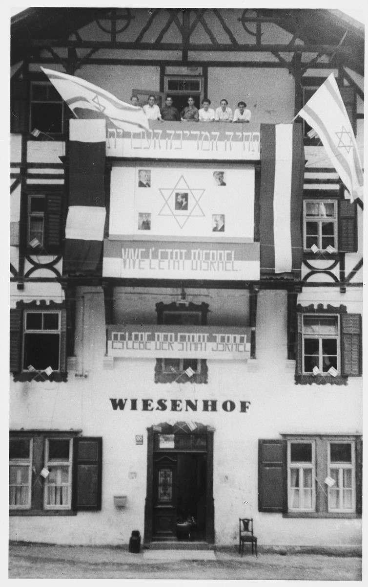 Jewish DPs pose on the balcony of the Wiesenhof DP center in Gnadenwalde which is decorated with flags and banners in celebration of the declaration of the State of Israel.