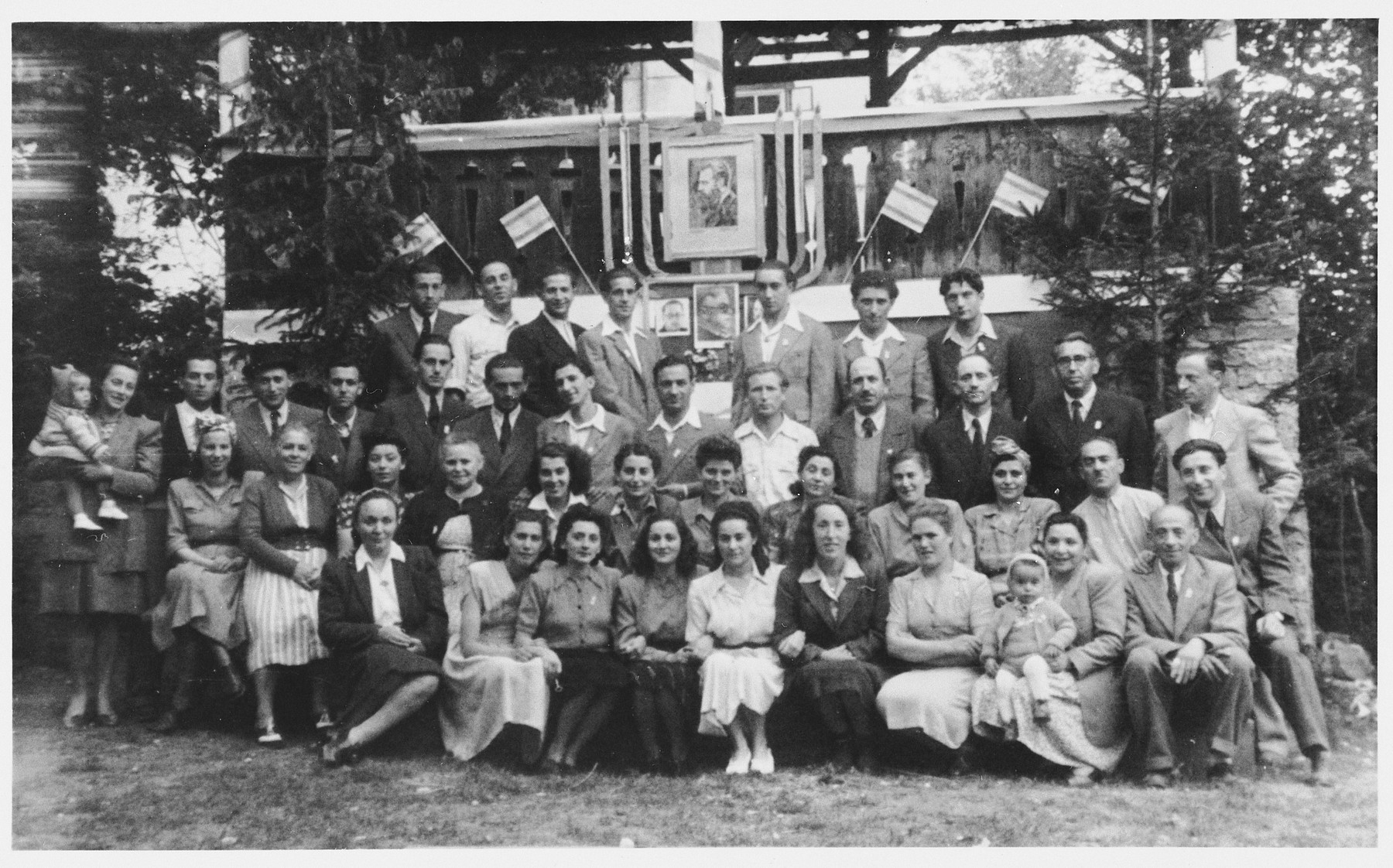 Group portrait of Jewish DPs outside the Wiesenhof DP center in Gnadenwalde, which is decorated with flags and portraits in celebration of the declaration of the State of Israel.