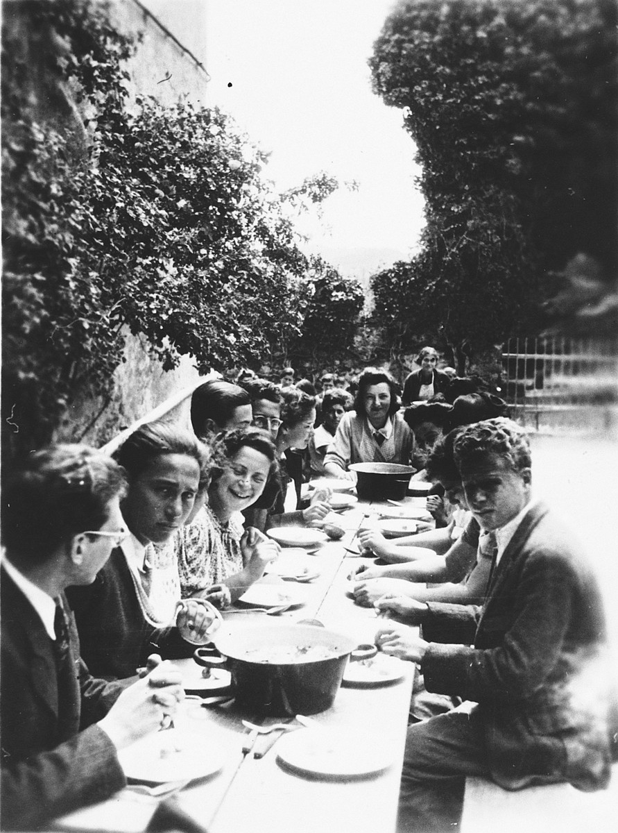 Older children eat a meal outdoors in Chateau de la Hille.  Pictured on the left (front to back) are Walter Kamlet, Peter Landesmann, Inge Schragenheim, unidentified, Kurt Moser, Edith Moser, unidentified.  On the right front is Edgar Chaim.  Standing in the rear is Ruth Klonower.
