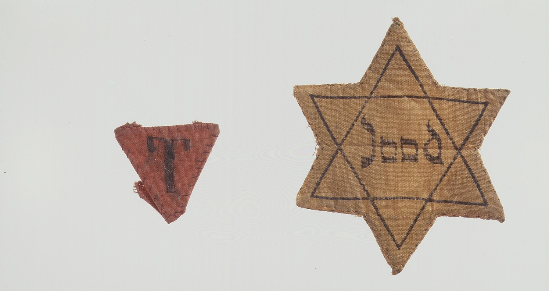 Composite photograph of two badges: (1) a triangular concentration camp prisoner badge with the letter T for Tschechoslowakei (Czech) issued to Czech political prisoner Karl Bruml, and (2) a Dutch Jewish star with the word Jood (Jew) printed on it.