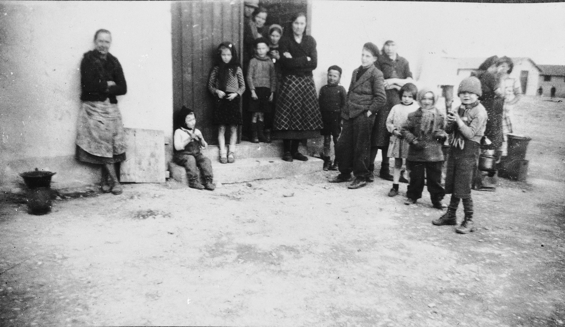 A group of women and children stand in the doorway of a barracks, likely in the Rivesaltes internment camp in France.