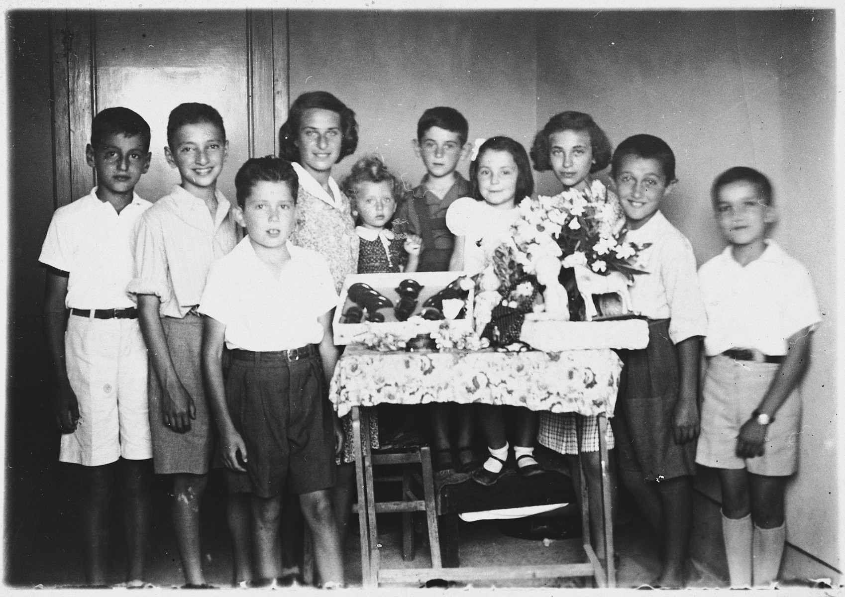 Group portrait of Jewish refugee children at a birthday party in Kavaja, Albania.  Pictured from left to right are: unknown, Marki Azriel, Michael Levy, Stella Gershon, Ela Mandil, Gavra Mandil, Irena Mandil, unknown, Michael Konforti, Jasa Altarac.  The party was in celebration of Irena Mandil's birthday.