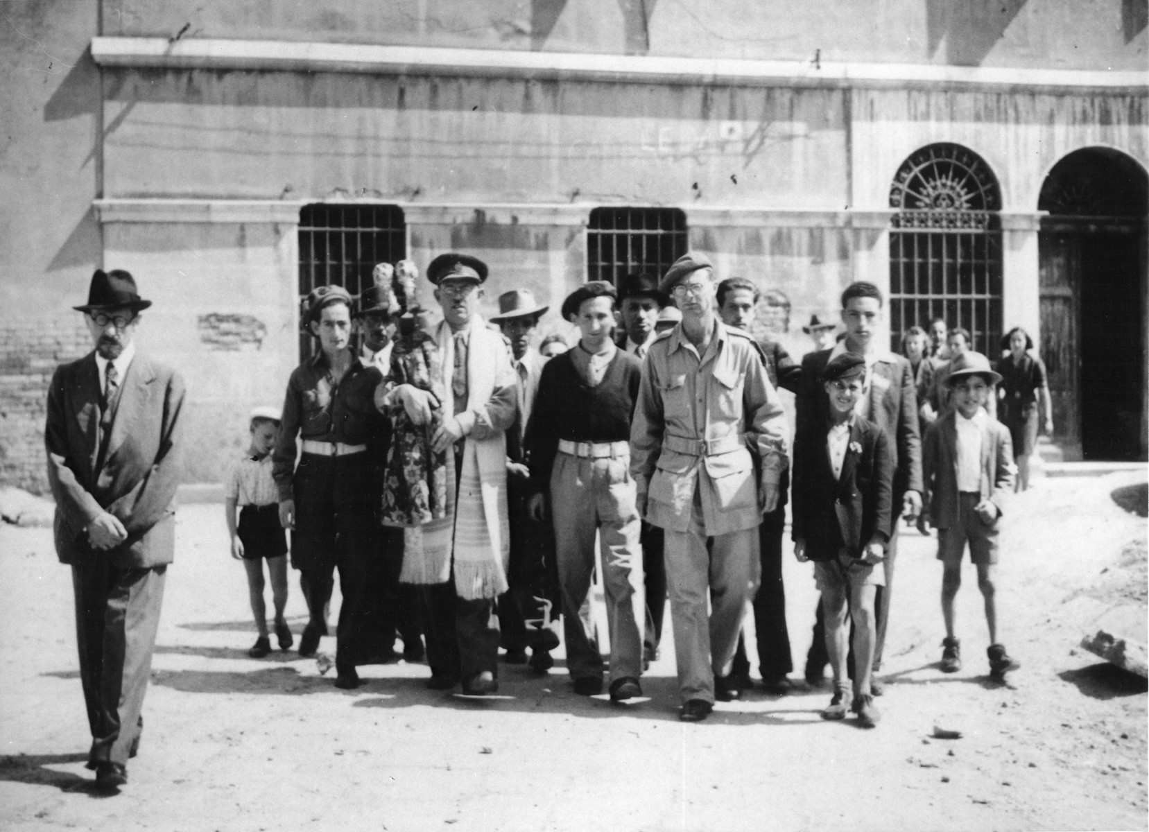 Rabbi Lifschitz, in the company of Jewish Brigade soldiers, carries a Torah scroll that has been rescued, to the Sephardic synagogue in the Venice ghetto.  Also pictured is Immanuel M. Ascarelli (second from the right) wearing a Jewish Birgade uniform..