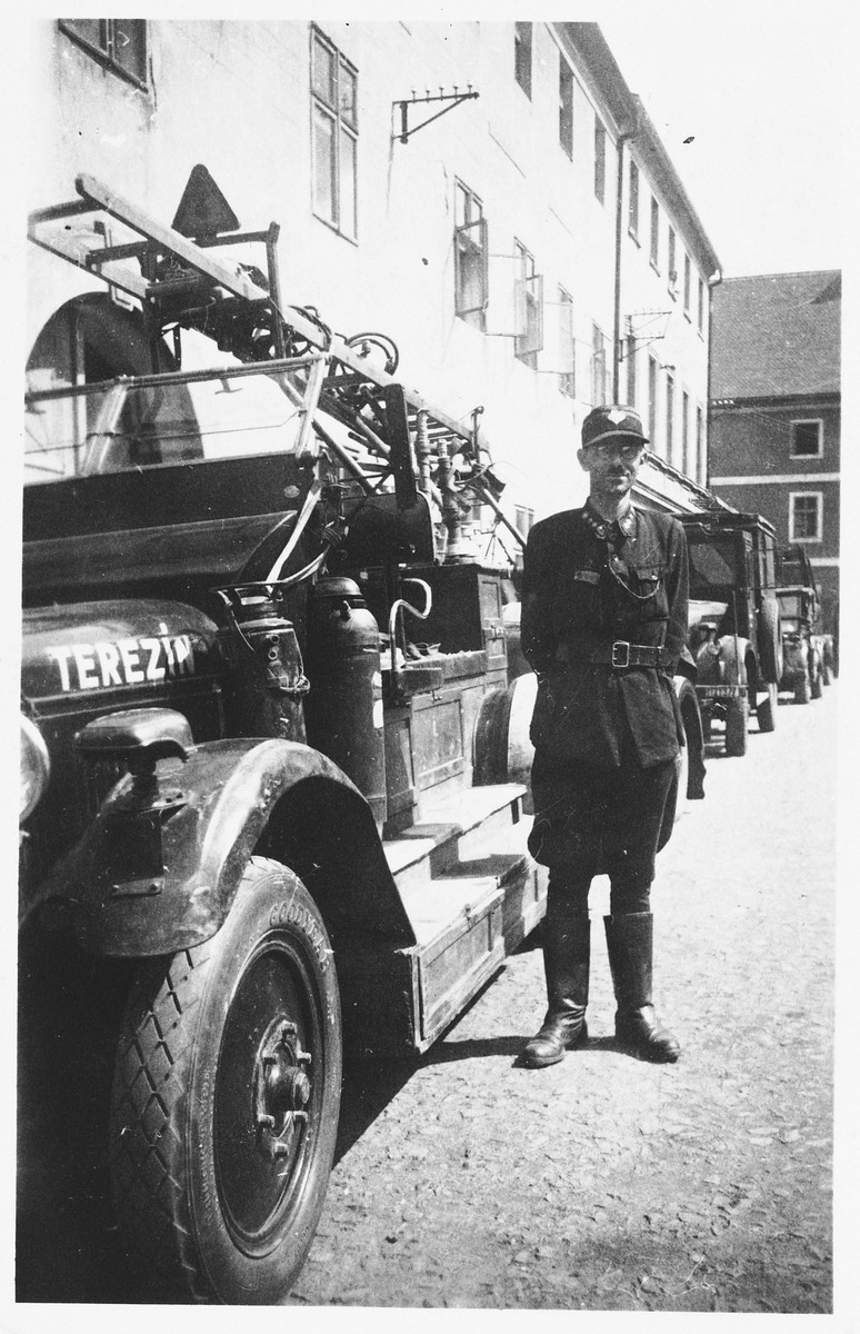 """Leo Holzer, chief of the Theresienstadt fire brigade, poses next to a fire truck marked Terezin on the hood.  The photo was sent Pavel Torsch, his former colleague in the fire brigade.  The inscription on the back of the photograph reads: """"To my dear friend and companion of my youth with heartfelt wishes! [signature unclear], 27.IX.1945."""""""