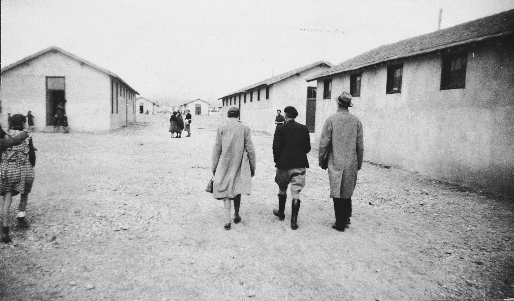 Three [visitors] walk along a street between rows of barracks in the Rivesaltes internment camp in France.