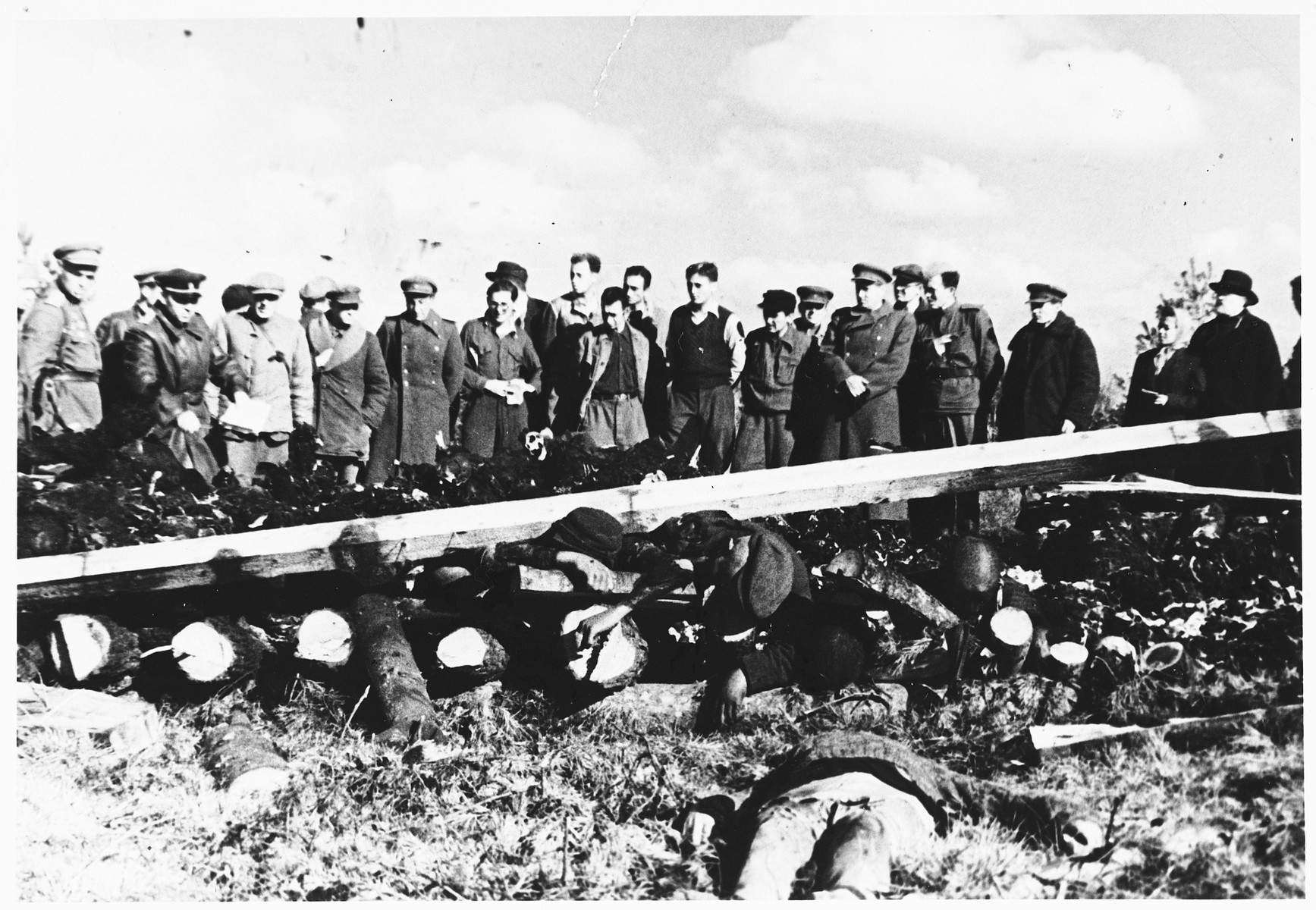 Soviet war crimes investigators view the corpses of prisoners in the Klooga concentration camp that have been stacked on a pyre for burning.