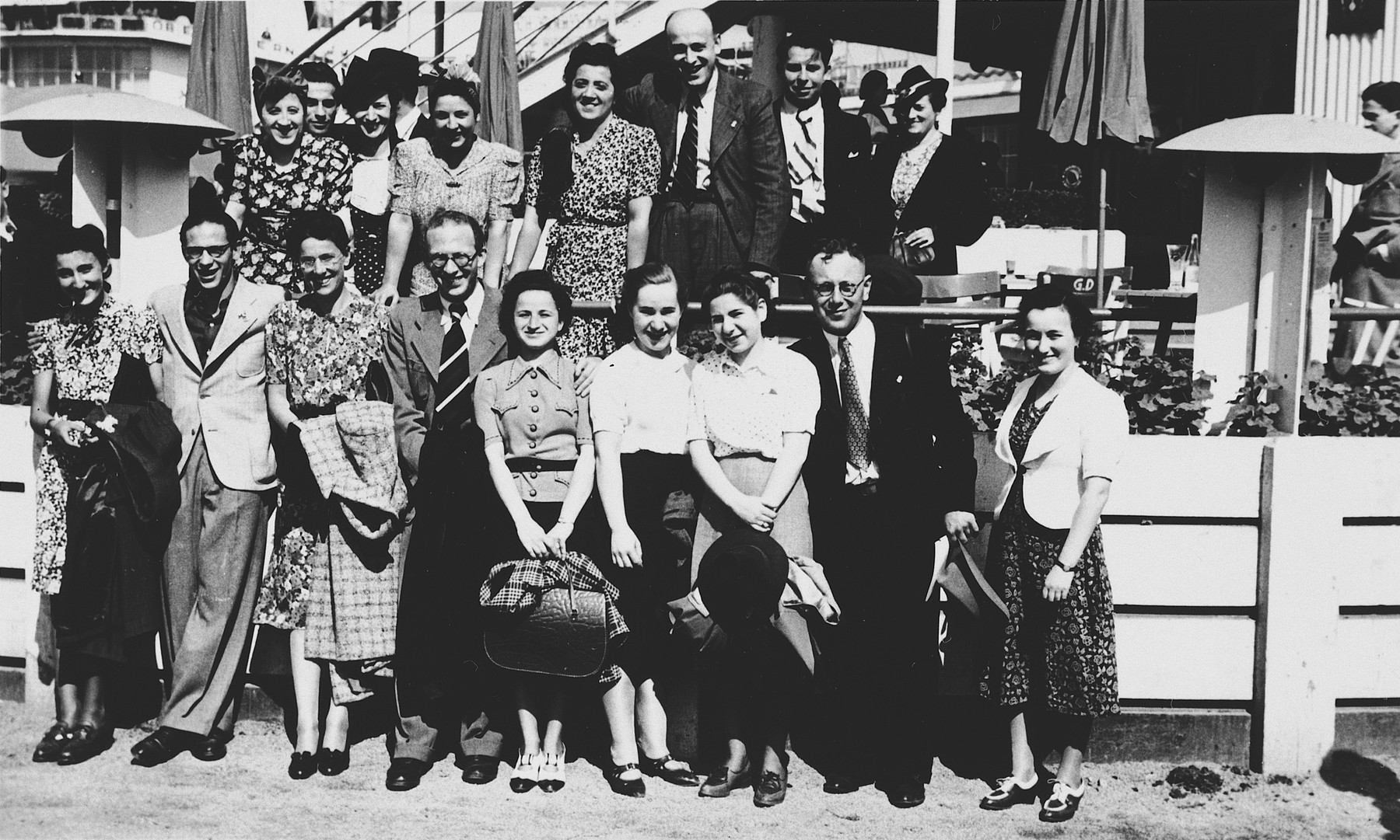 Group portrait of young men and women in front of an outdoor cafe in Luxembourg.  Among those pictured is Magdalena Nussbaum (top row, left).