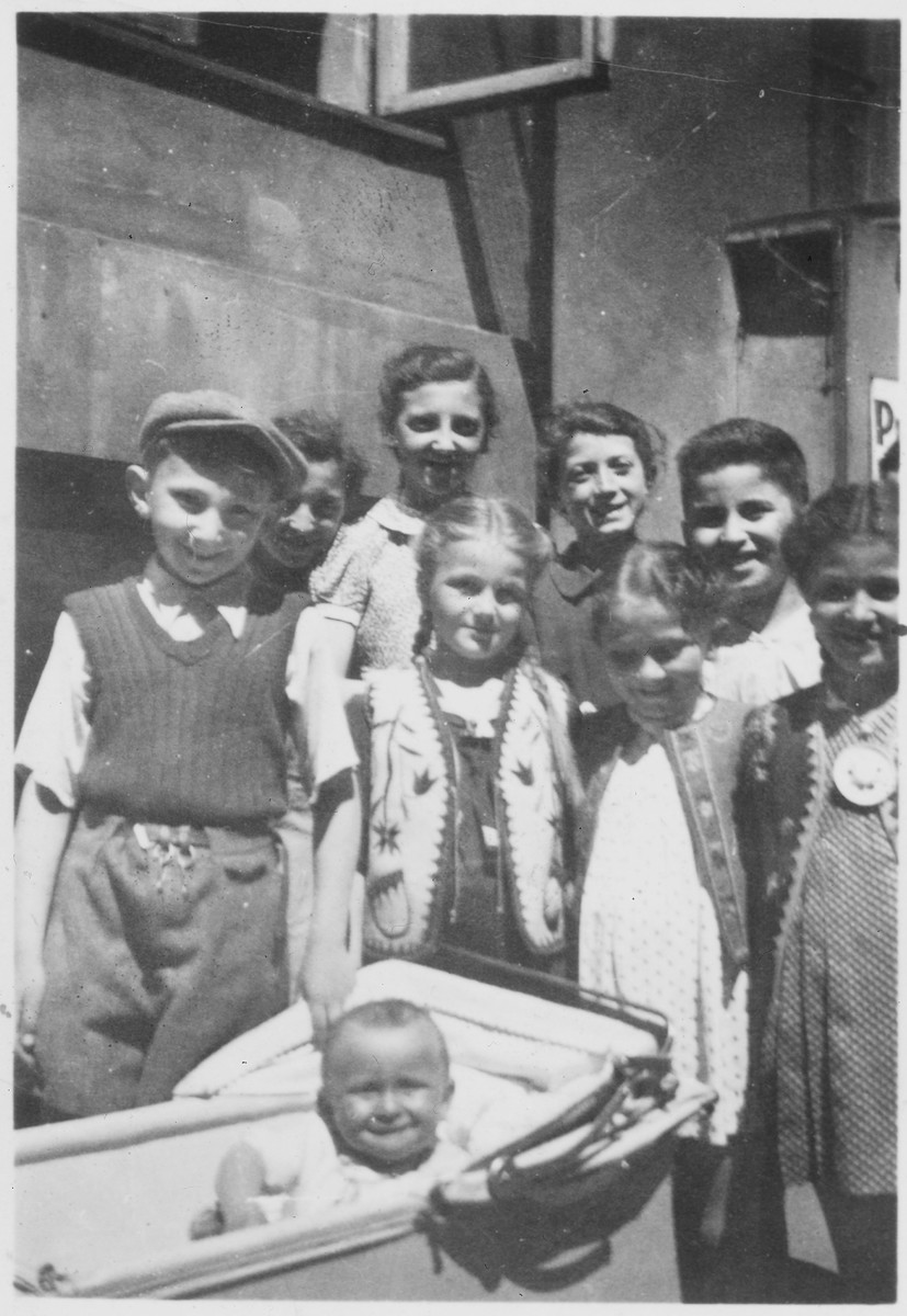 Group portrait of Jewish children in the Warsaw ghetto posing around a baby in a carriage.  Among those pictured is Leo Arnfeld.