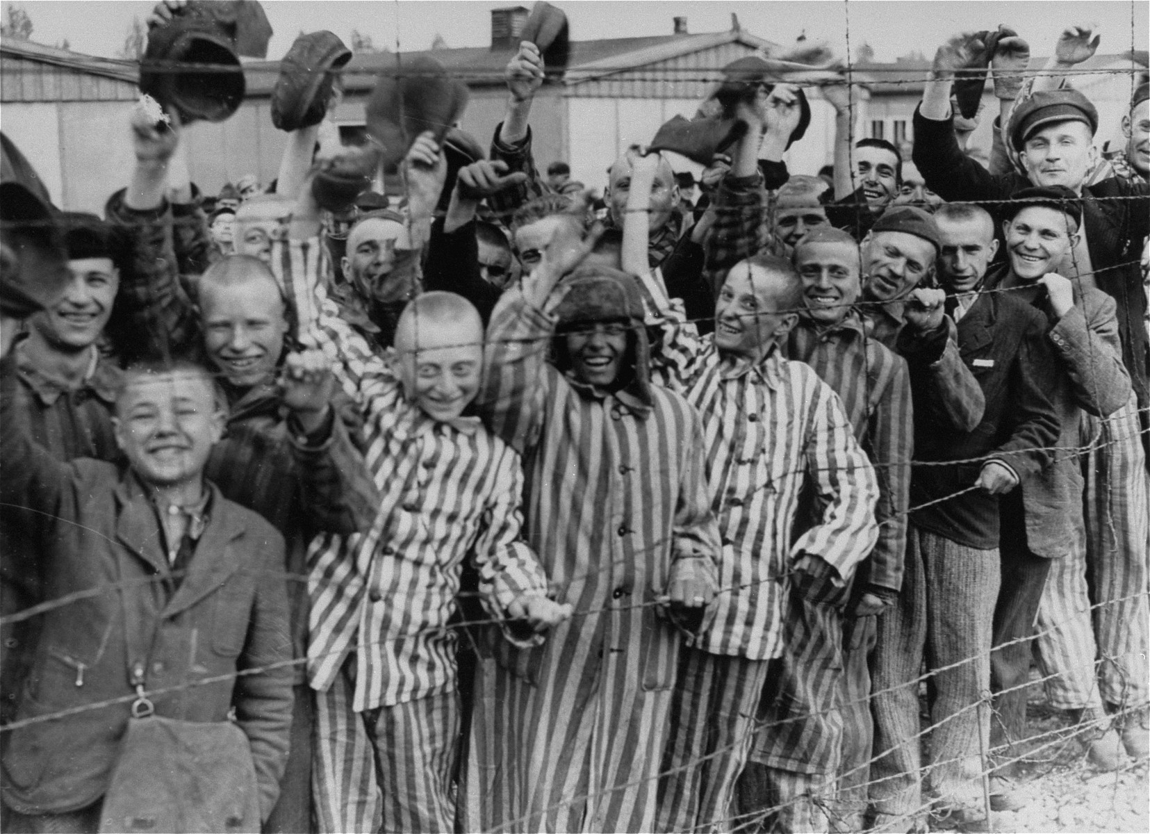 Young and old survivors in Dachau cheer approaching U.S. troops.    Among those pictured are Juda Kukiela (middle), Tevya Grojs (second from the right), David Moszkowicz (fourth from the left), and Gyorgy Laszlo Spiegel (second from the left).  Dirk Keern (far right, waving) was a Dutch political prisoner.  The boy third from the left has been identified as both Szmulek Rosental and as Josek Lerer.  The man on the far left has been identified as Alan Weisfeld.