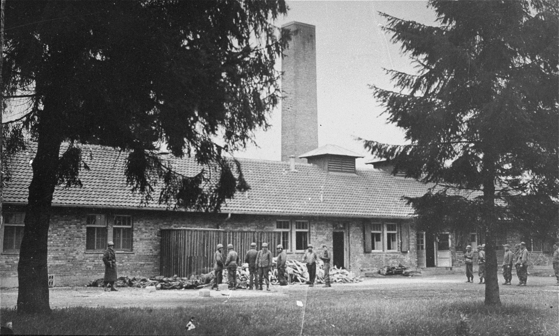 American soldiers in front of the crematorium in Dachau.  The corpses on the left are of SS personnel summarily executed by American troops.