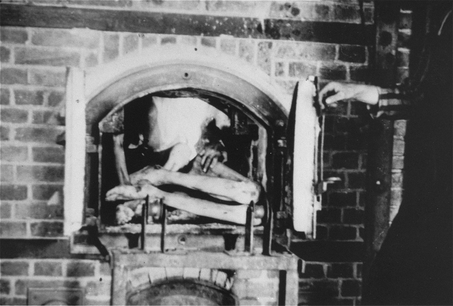 A corpse in a crematorium oven.  This photo was taken by William Landgren who arrived with his unit 30 minutes after the liberation of the camp.  The next day his unit was ordered back to help police the camp.