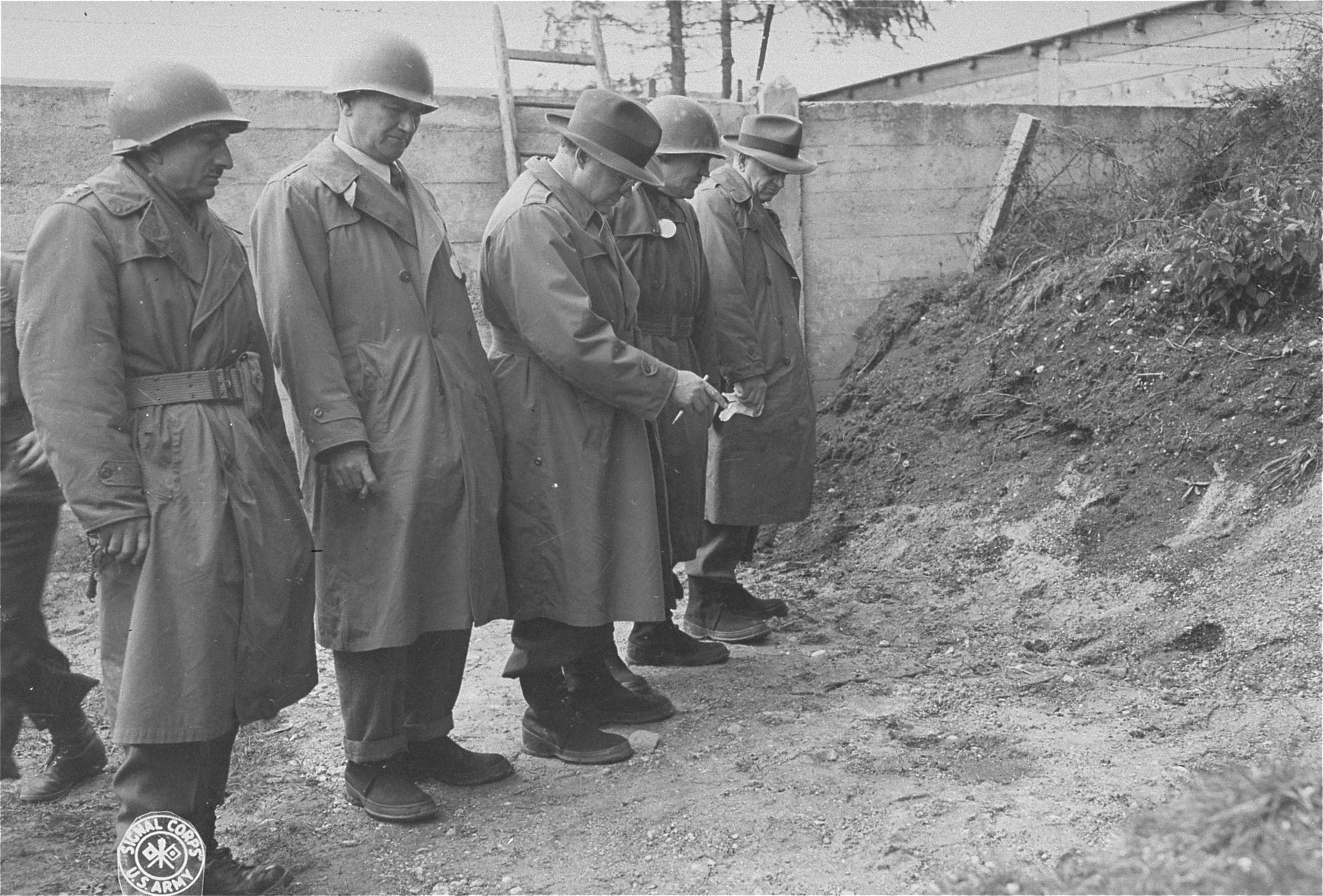 Members of a U.S. Congressional party investigating Nazi POW atrocities view a spot where POWs were shot.  Sen. C. Wayland Brooks points to a spot saturated with blood. With him are Maj. Gen. Wilton B. Persons, who is conducting the tour, Rep. James Richards, Rep. John Vorys, Sen. James Richards and Sen. Kenneth S. Wherry.