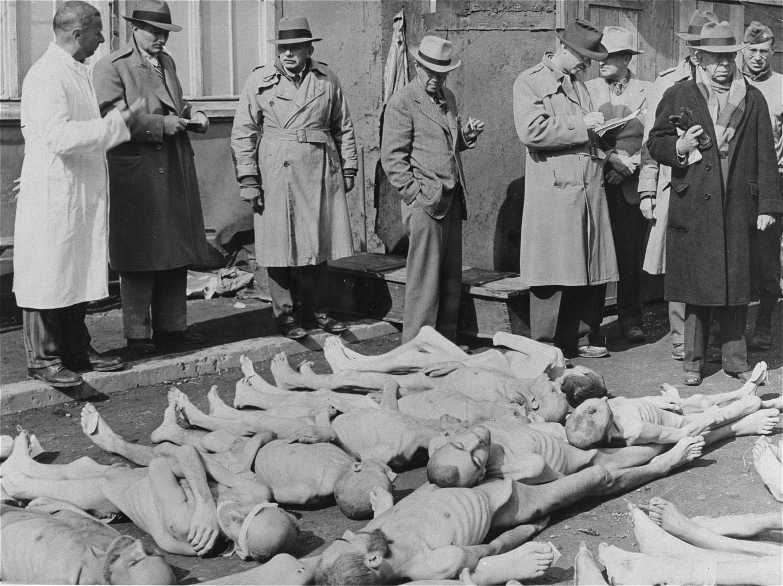 A group of American editors and publishers in Dachau are shown the corpses of prisoners during their investigation of the camp.