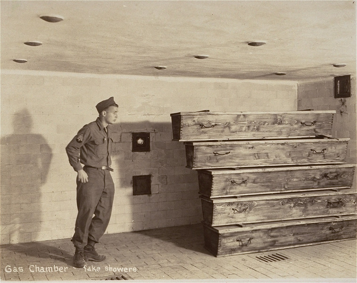 An American soldier inside the gas chamber at Dachau.  Fake shower heads can be seen on the ceiling, while on the right coffins are visible.