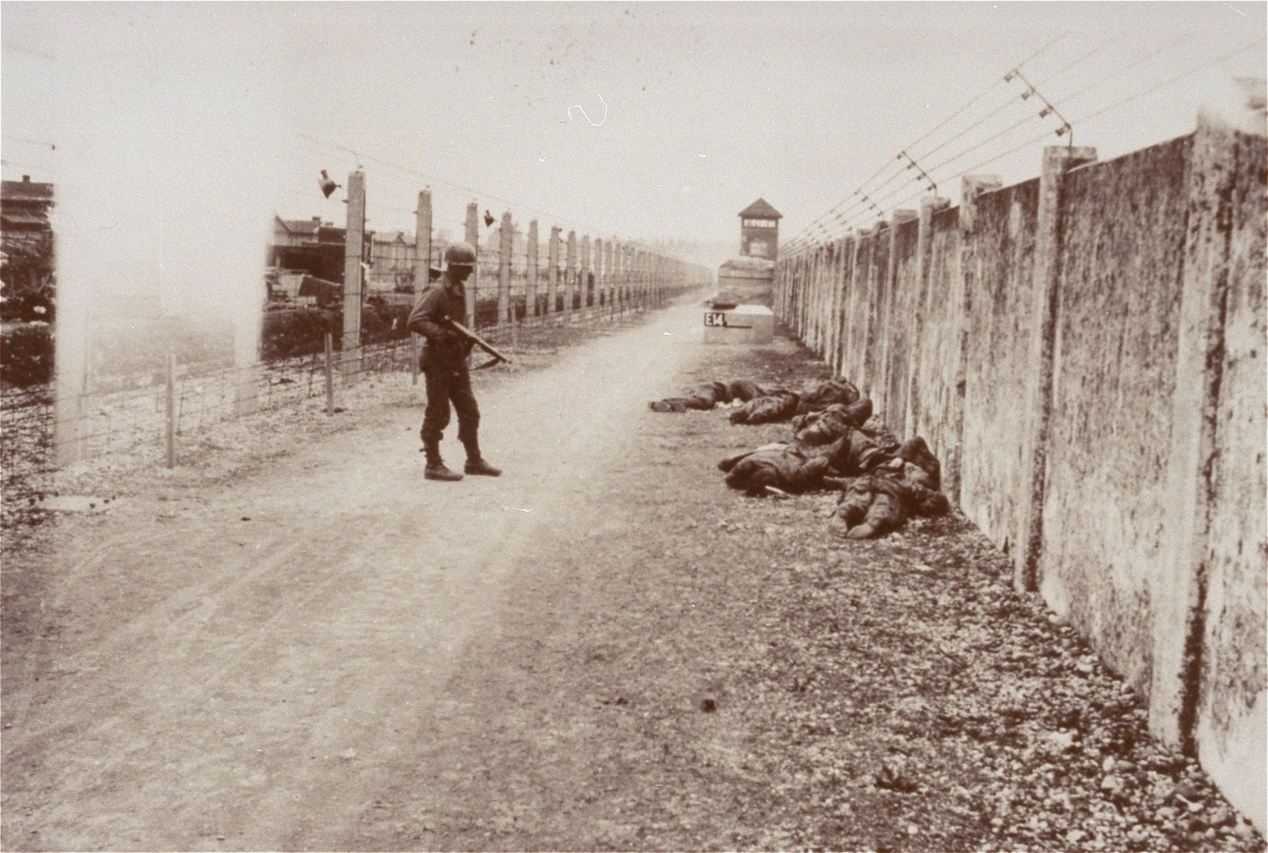 An American soldier stands near the corpses of Dachau guards who were executed just after the liberation of the camp.