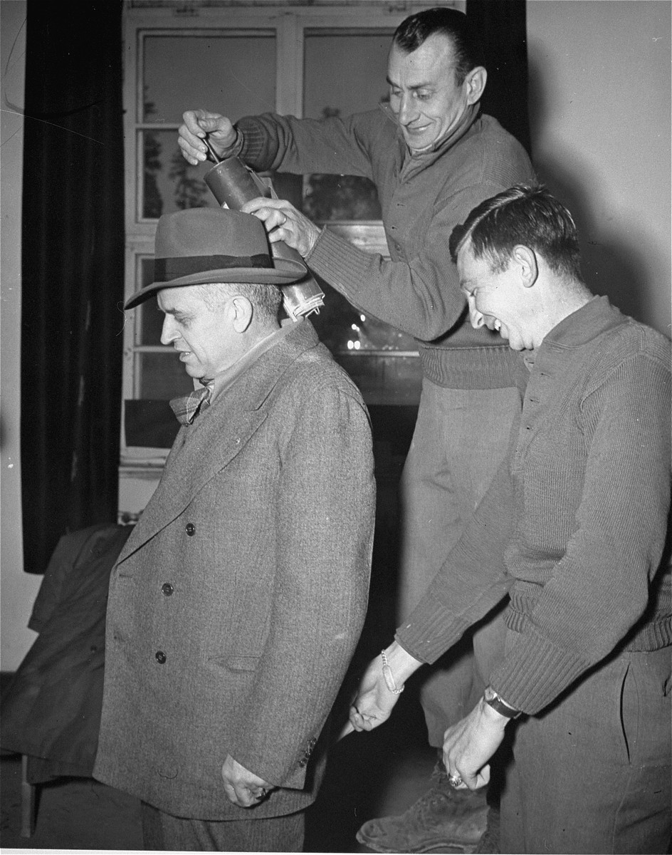 Sen. Kenneth S. Wherry (R-Neb), a member of the Congressional party investigating POW atrocities in Germany, receives a shot of de-lousing powder (as an antidote against typhus) as he leaves infamous Dachau prison camp after he and his party investigated conditions there.