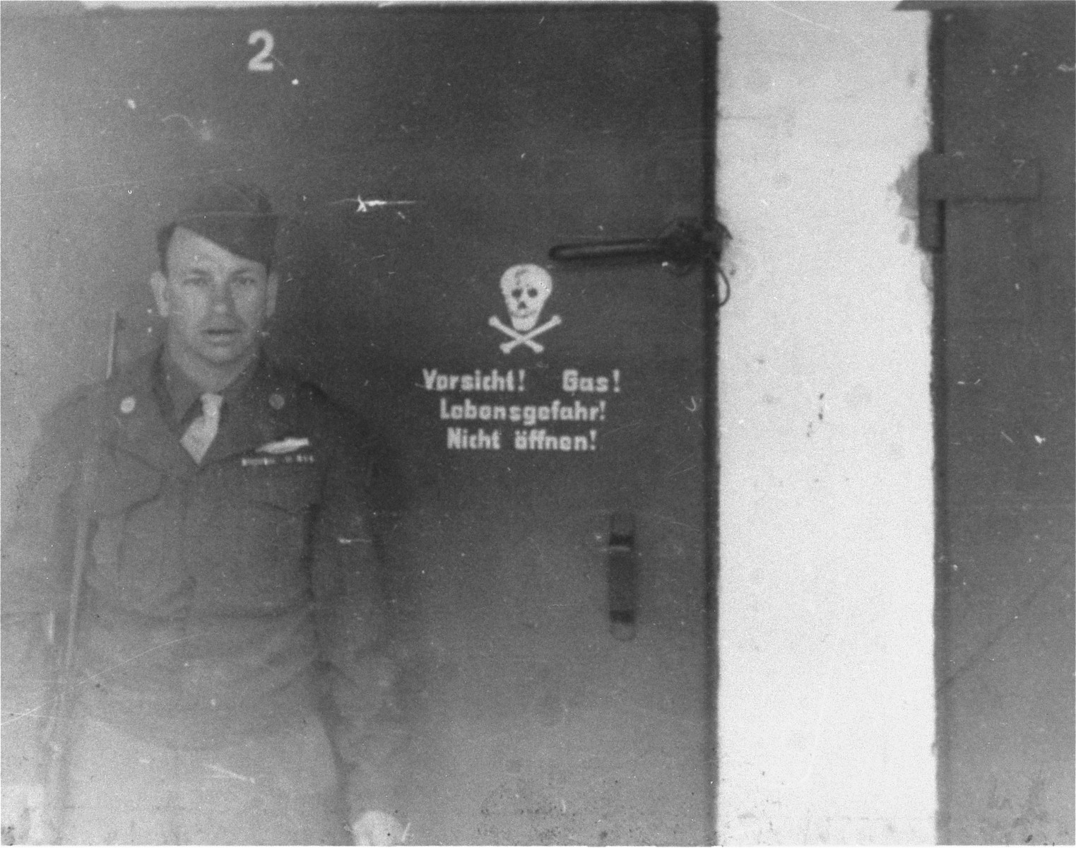 An American soldier stands outside of the gas chamber in Dachau.