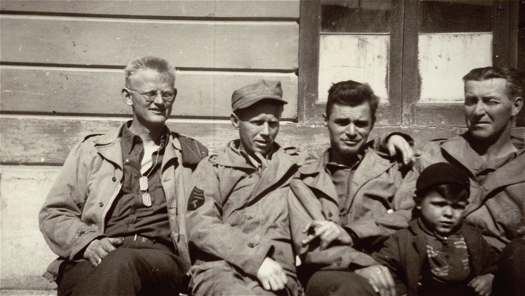 American soldiers in Dachau pose with a young survivor.  On the far right is Elton Cooper, US army.