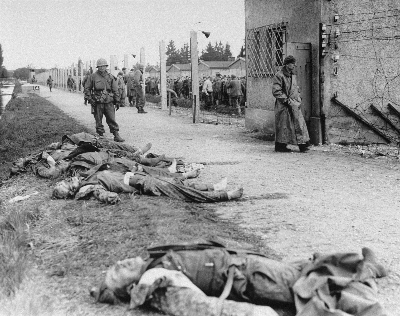 An American soldier stands beside the bodies of SS personnel shot by U.S. troops during the liberation of Dachau.    The boots have been stripped off of the bodies.