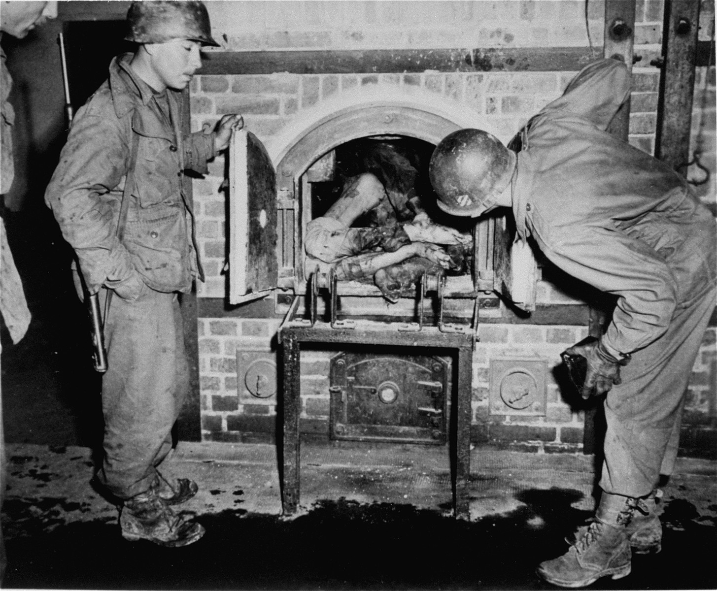 American soldiers inspecting the crematorium in Dachau.  The corpse was put into the ovens after liberation to simulate the operation of the furnace.