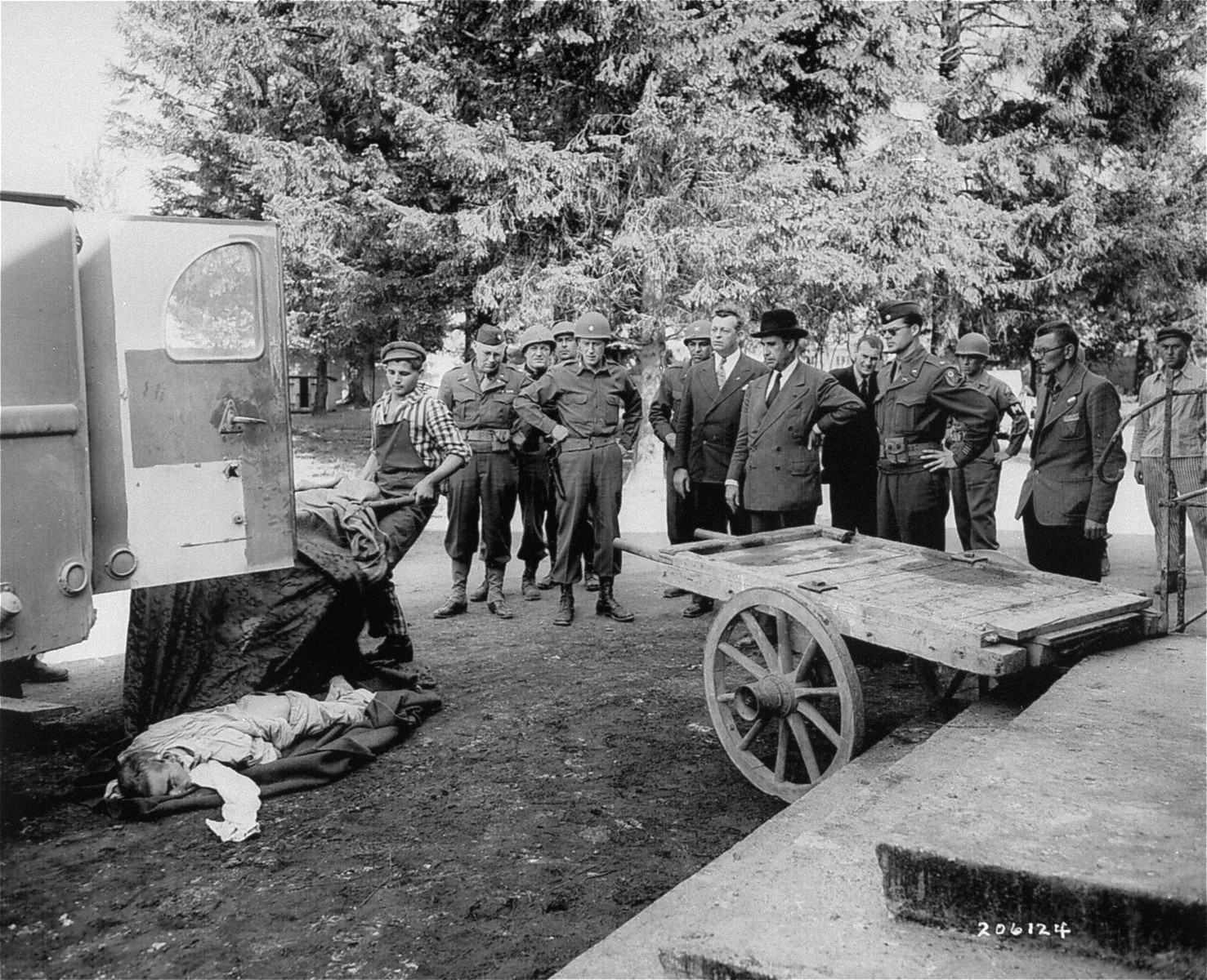 Congressmen Evertt M. Dirksen and John S. Young, escorted by Maj. William Bodine, Jr., view bodies of former prisoners in Dachau.
