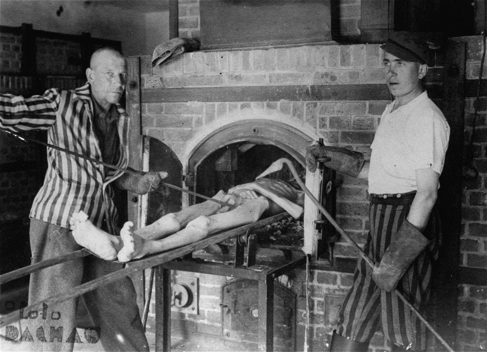 Survivors of the Dachau concentration camp demonstrate the operation of the crematorium by pushing a corpse into one of the ovens.