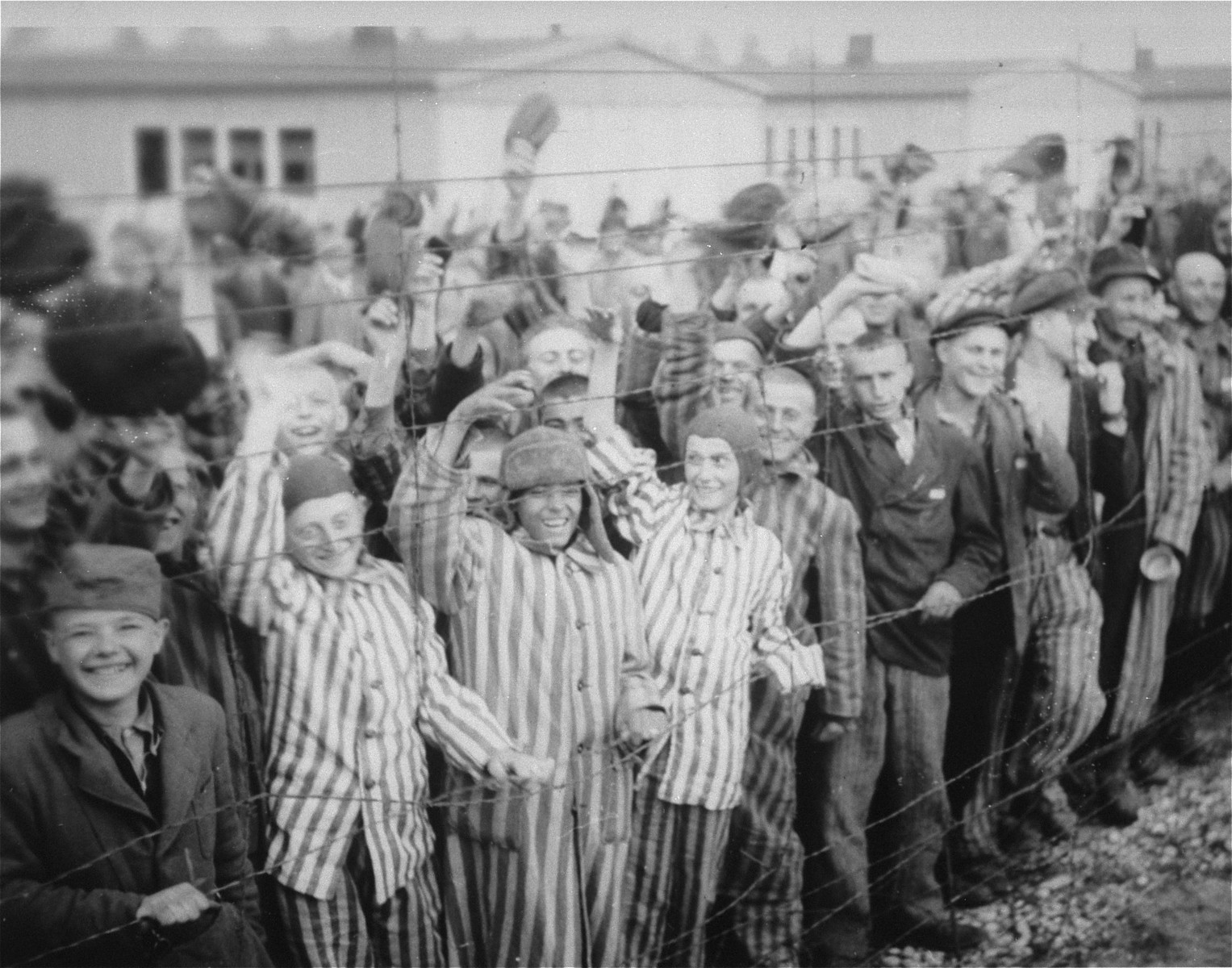 Young and old survivors in Dachau cheer arriving U.S. troops.    In the middle stands 18 yr. old Juda Kukiela, the son of Mordcha Mendel and Ruchla Ita.  Second from the left is Gyorgy Laszlo Spiegel (b. 5/25/30) from Budapest, Hungary.