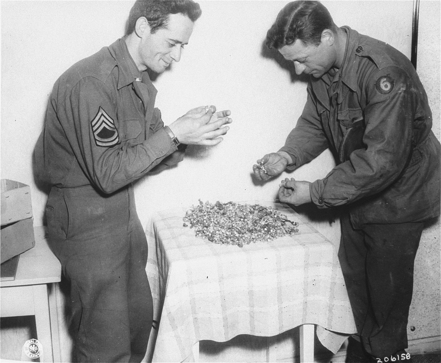 Tech Sgt. Claude L. Campellone (left) and Tech 4 Charles Henry look over the gold fillings that were found in Dachau.  The fillings were removed by the Germans when the prisoners died or were killed.