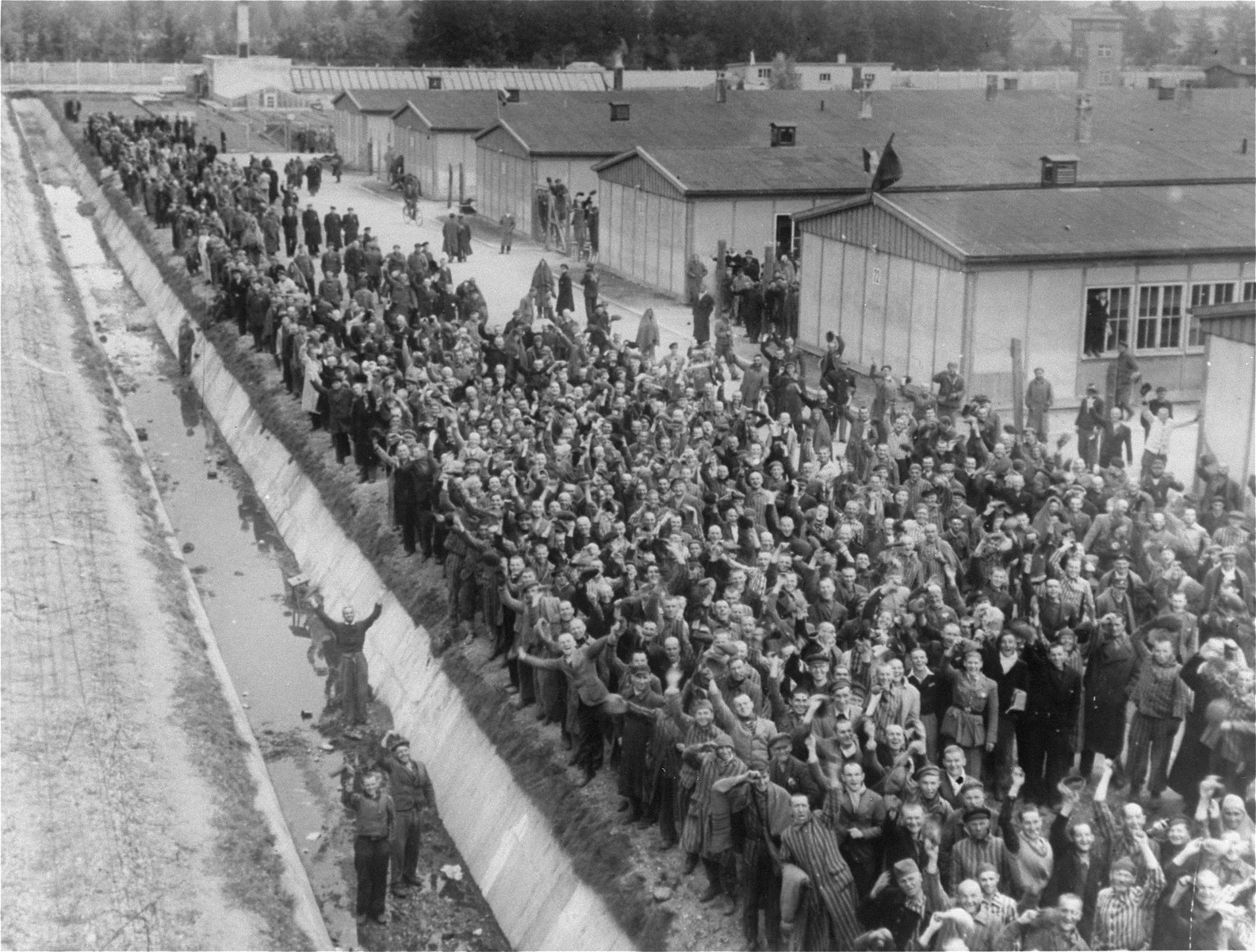 Dachau survivors gather by the moat to greet American liberators.
