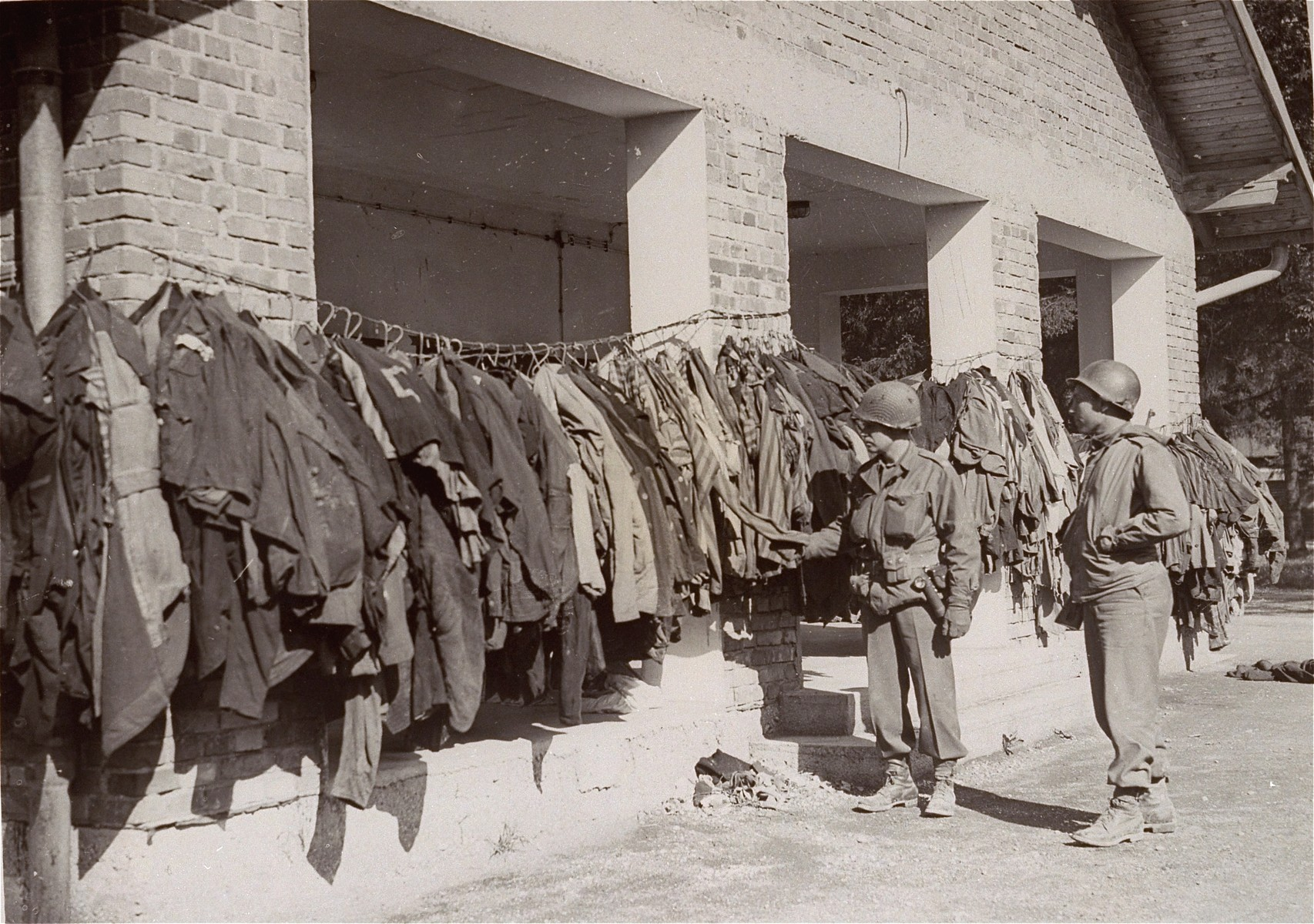 "Two American soldiers examine disinfected prisoner uniforms in Dachau.  Original caption reads: ""Dachau Concentration Camp.  Horrors worse than those found in the German concentration camps of Buchenwald and Belsen were discovered in the stinking hell-hole of Dachau, captured by troops of the 42nd and 45th Infantry Divisions of the Seventh U.S. Army April 30, 1945.  More than 32,000 prisoners were liberated, among them some Englishmen, Canadians and Americans.  The camp was formally surrendered by an SS lieutenant carrying a white flag, accompanied by a Swiss Red Cross official, but SS troops opened fire as American troops approached the main entrance.  The Germans were shot down.  Three prisoners were electrocuted when they tried to burst through the electrified wire barrier to welcome the Americans.  SS guards opened fire on other prisoners who went wild with joy and rushed to meet the liberating troops.  Prisoners with access to records said 9,000 people died of hunger, disease or shooting within the past three months at Dachau.  Four thousand more perished during cold Winter months.  When Americans entered the camp, they found 50 open railway cars standing on a siding, apparently full of dirty clothing but actually found to contain hundreds of corpses piled on top of each other.  They also found a row of kennels where fierce dogs were kept to set after escaping men.  They discovered gas extermination chambers, incinerators full of naked bodies, bodies marked for dissection and the bodies of several small children.    This photo shows: Soldiers of the Seventh U.S. Army inspect the clothing of dead prisoners hanging outside the Dachau crematory.  Although alive with lice, they were given to new prisoners, whose better clothing was distributed to German civilians."""